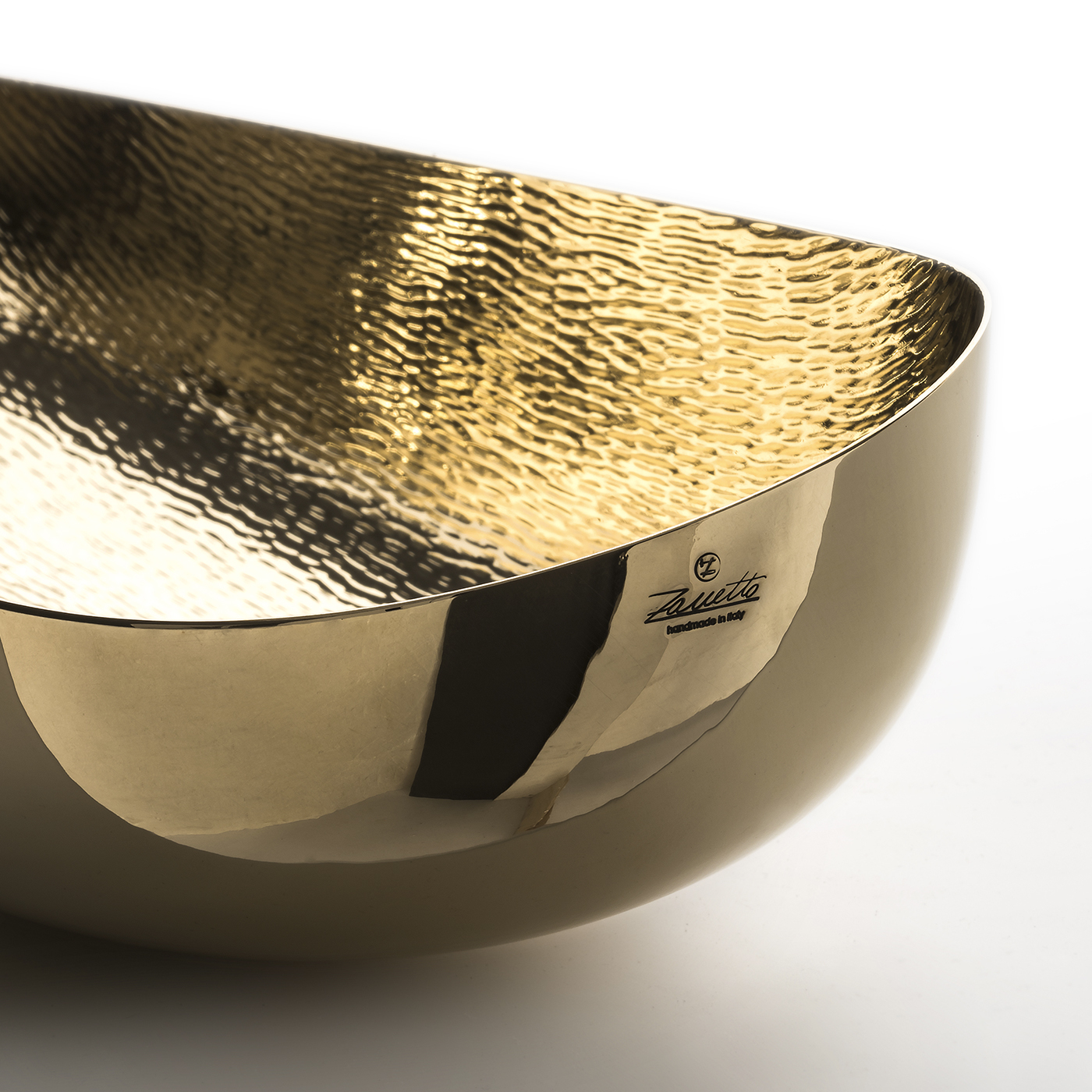 Illusioni Bowl - The organic look and feel of this bowl make it a special piece to display in any room in the house to make a sophisticated and elegant statement. Made entirely of brass with a beeswax coating, its elongated, sinuous shape and its generous size give this object of functional decor a versatile quality. Its smooth exterior surface strikingly contrasts with the lightly textured interior for a modern final effect.