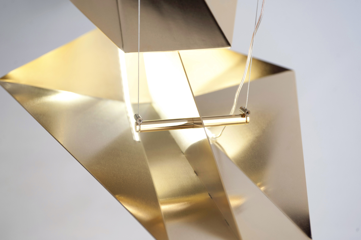 Orion Chandelier - Gold Limited Edition - <p>Orion is a sculptural lamp, featuring a design standing out in space with its multifaceted geometry, which diffuses light thanks to an array of LED strips, and releases a magical display of light into the ambient, playing with the reflections of the gilded metal. It consists of a series of 2 mm thick steel plates, which are laser cut, bent and shaped, welded and milled, then hand finished, to obtain a soft, reflective but not mirror-like satin finish. ​The Orion Gold Edition is available in a limited edition of 33 signed and silkscreened pieces.</p>