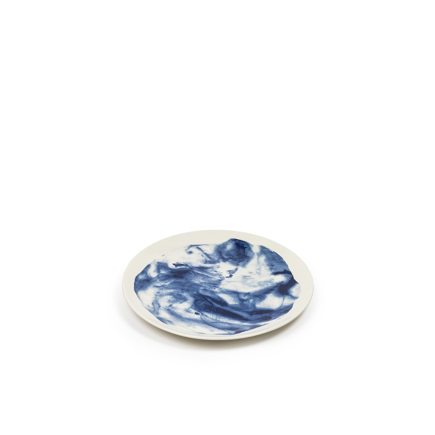 Indigo Storm Dinner Plate - Faye Toogood's range of ceramic designs for 1882 Ltd. celebrates the serendipitous beauty of natural imperfections. Indigo Storm, a new interpretation of traditional creamware forms, draws upon the chance patterns created when pigment added to the slip coating does not fully blend. The whorls and eddies resulting from these experiments, like meteorological formations in miniature, make up the collection's central motifs, appearing on pieces including plates, bowls and cups. Representing a streamlined take on our ceramic heritage, the fine earthenware employs the familiar tones of English Delftware: cream offset with a rich, deep blue. Dishwasher and Microwave safe.