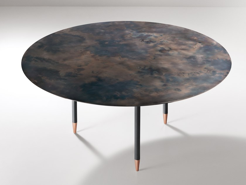 Roma Round Table - A table that interprets the round, spacious form of a brazier, which it echoes in its size and volume.‎ A symbol of sharing and communion that references the ritual of conviviality and spending time together.‎ The top, in generous proportions, and the lower 'lens' fuse into a single piece, into which three legs are inserted.‎ The personality of this sculpture-table arrives via the iridescent finish of the top, the memory of always-glowing embers, and the luminosity of the copper feet upon which the legs rest, lightening our perception of the whole.‎