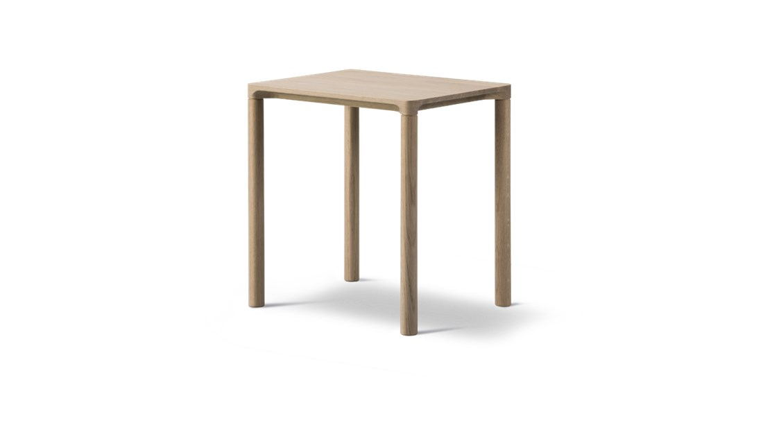 """Piloti 6700 Side Table - Piloti is a series of solid oak side tables. The subtle detailing of the table top creates the impression of a single line, floating between four delicate legs. The tables are supplied in two heights and can be combined as a nest.  The word """"piloti"""" refers to the pillars or columns that elevate a building above the ground. While the legs of our Piloti Tables resemble pillars, the overall intention is for the table to appear like a slim line almost floating in space.   An elegant integration of the table top with the legs ensures a subtle, streamlined transition into one balanced entity.   Light in appearance yet sturdy in construction, the Piloti tables in wood are made from solid oak, a naturally beautiful, tactile material that needs no adornment. The option of different sizes gives you the freedom to cluster the tables together in a corner or as part of a sofa set-up. Place them individually as side tables or as a matching pair on either side of a bed.   