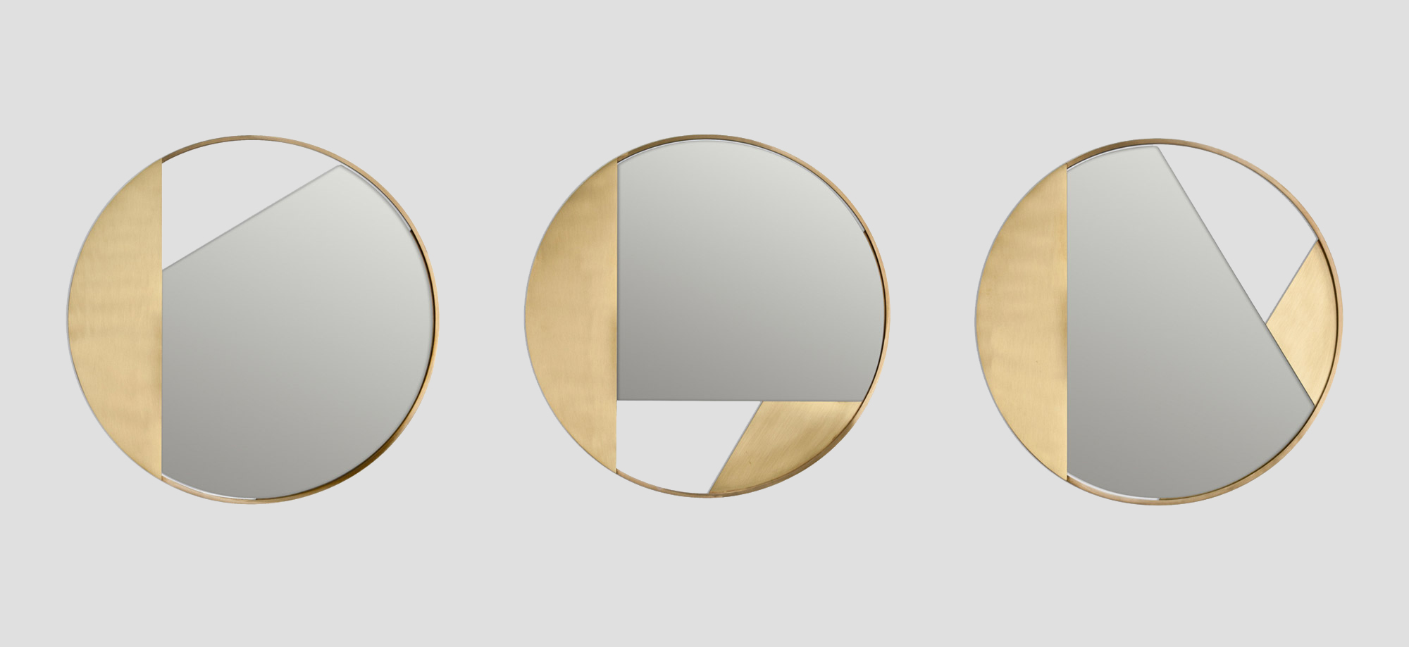 Revolution Mirror no.3 - Three wall mirrors characterized by a clean and rigorous design. The frame in brushed brass encloses a round mirror, mounted at different angles to create a new design every time. The balance created between the parts creates a delicate graphic effect that transforms the mirror into a sort of wall jewel. Handmade in Italy by skilled craftsmen. 