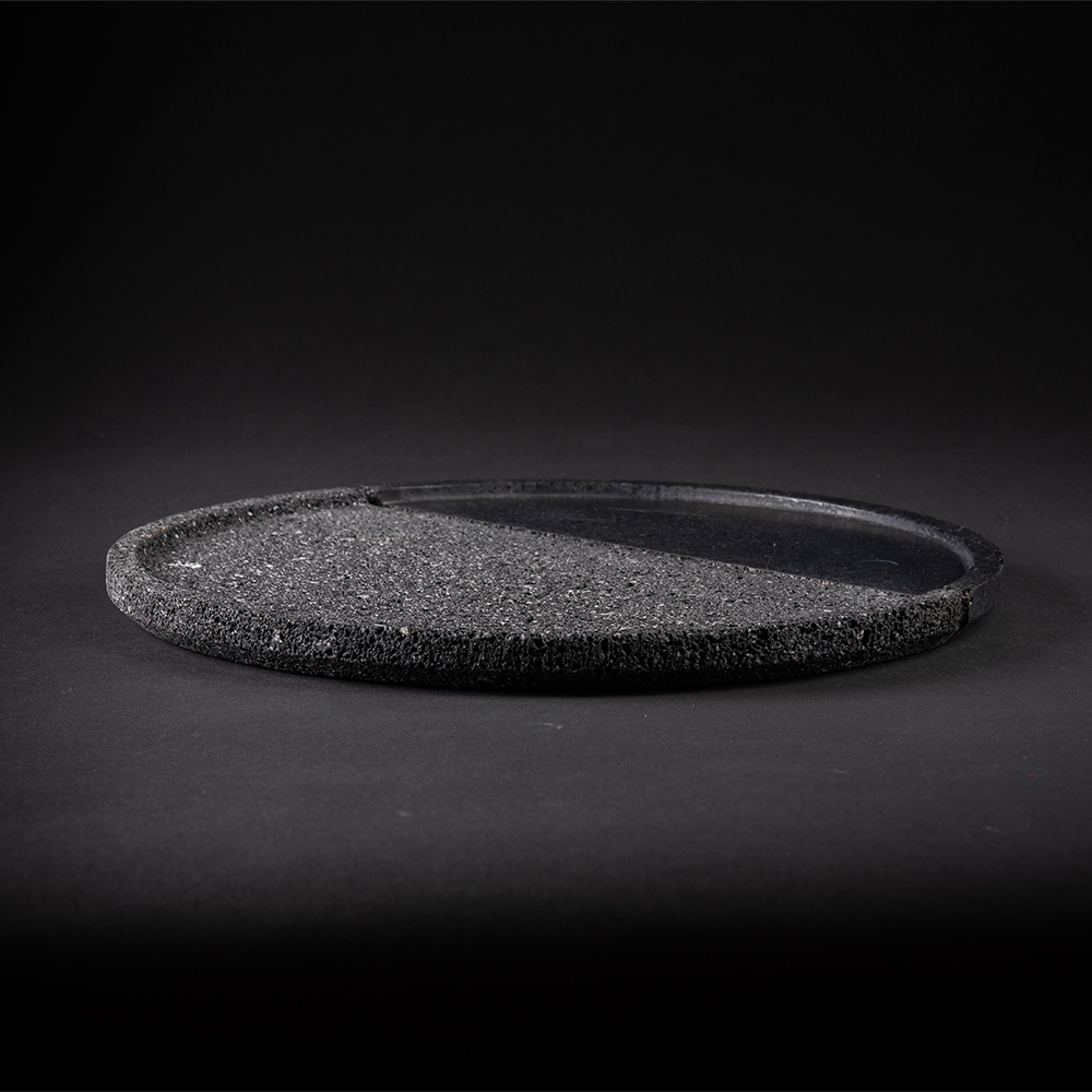 Lava Round Tray  - Volcanic rock is a witness to the power of nature: hand–polished by craftsmen with a millenary tradition, its unruly nature is transformed into a sensible and human object. With it's dual texture, the Lava large plate is as much an homage to Mexican tradition as it is a glance in the direction of modernity. 