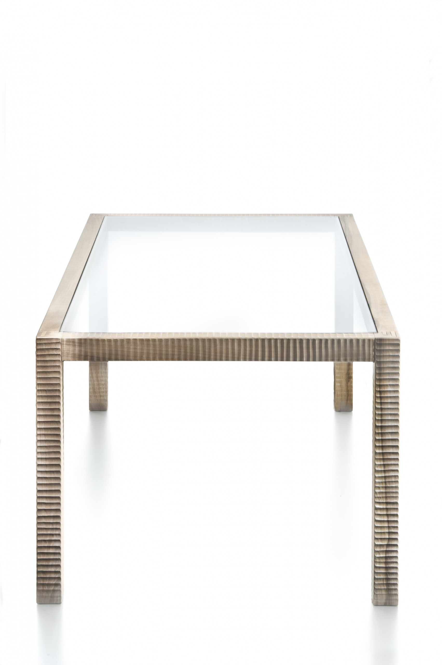 """Pisano Dining Table - <p>Pisano is a table whose structure is made with interlocking joints, hand-finished on all sides by planing.<br /> The top is made of 2 cm thick extra-clear glass. The entire manufacturing and finishing process is carried out manually in our workshop. The wood used for this piece is Juglans Regia – common Italian walnut; not dried but """"raw"""". This wood belongs to the Latin tradition of furniture-making and features an extremely compact fibre which can, however, be worked without too much difficulty; it is therefore highly suitable for household items.<br /> Over time the wood hardens and becomes extremely resistant, and oxidises slightly to take on a progressively warmer amber colour. The intense rationality of the form flourishes and becomes exquisite at the four points where the legs are inserted with a three-way dovetail joint which is the only decorative feature.<br /> Customised and made with European cherry, Slavonian oak, maple.</p>  
