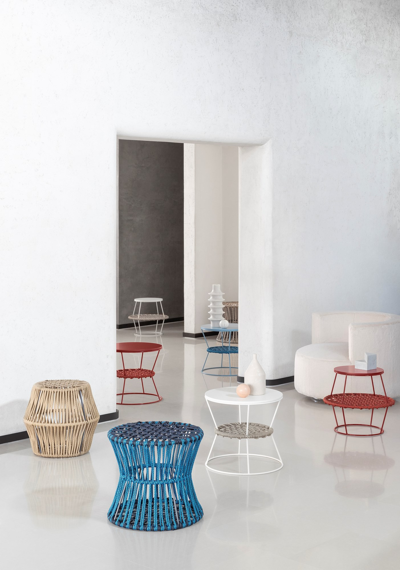 Ziggy Stool Hourglass - Ziggy is a round garden stool in polyester rope. Available in two variants.  Metal, wood, rope – simple materials which reinvent commonly used objects. A collection of poufs and coffee tables in metal rods and woven nautical cords, mixed together like the paints on an artist's palette. The reference to David Bowie's iconic Ziggy Stardust is no accident and relates to the irony in the idea of revolutionizing the type of accessory furniture in the area for relaxing. The barrel and hourglass silhouettes come together to make up islands which expand: interweaving and volumes are enhanced in the coordination of the mixed colors of the cord, pointing to a new idea of furnishing accessory with endless possibilities of personalizing the space. The two-tone plaited rope is an exclusive Saba combination. NB: The pouf (with a barrel and hourglass silhouette) is made of materials suitable for outdoor use.  Materials Structure in coated wire drawn with diameter 8 mm with plaiting of 6 mm diameter of polyester ropes. Finishing and ropes are suitable for outdoor use. The upper top surface of the low table is in MDF h 19 mn lacquered finish. | Matter of Stuff