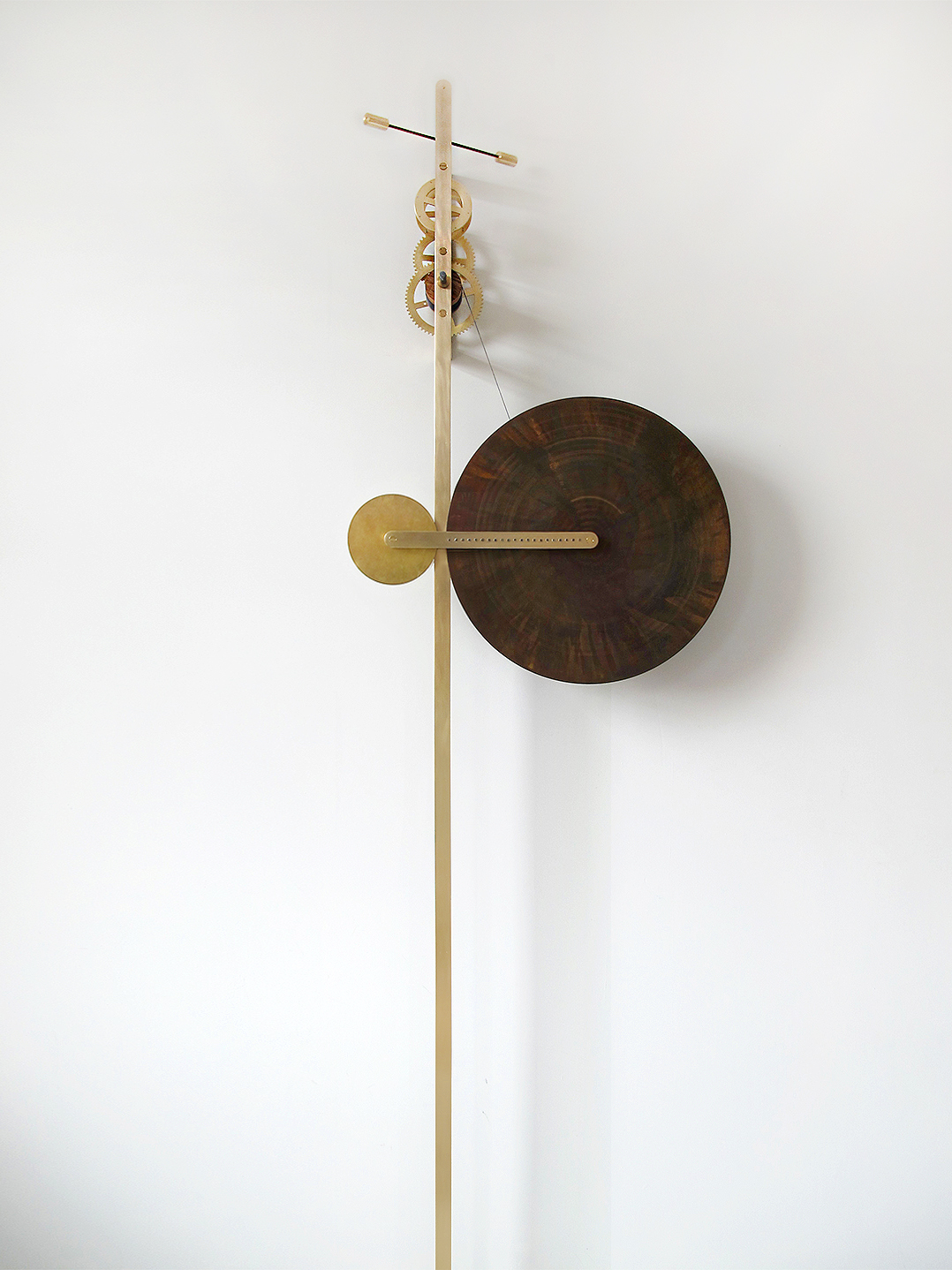 Clean Sweep Sculptural Piece - <p>Clean Sweep is a sculptural time piece composed of a large brass disc which rotates very slowly down a vertical stem, making one revolution over a period of approximately 12 hours. The brass disc is oxidised with a rich, coloured patina that is gradually cleaned away by brushes within the armature as the disc rotates on its journey downwards. Concentric rings of cleaned brass contrast with the patinated surface, offering a continually changing canvas and a different way to think about the passage of time. </p>  | Matter of Stuff