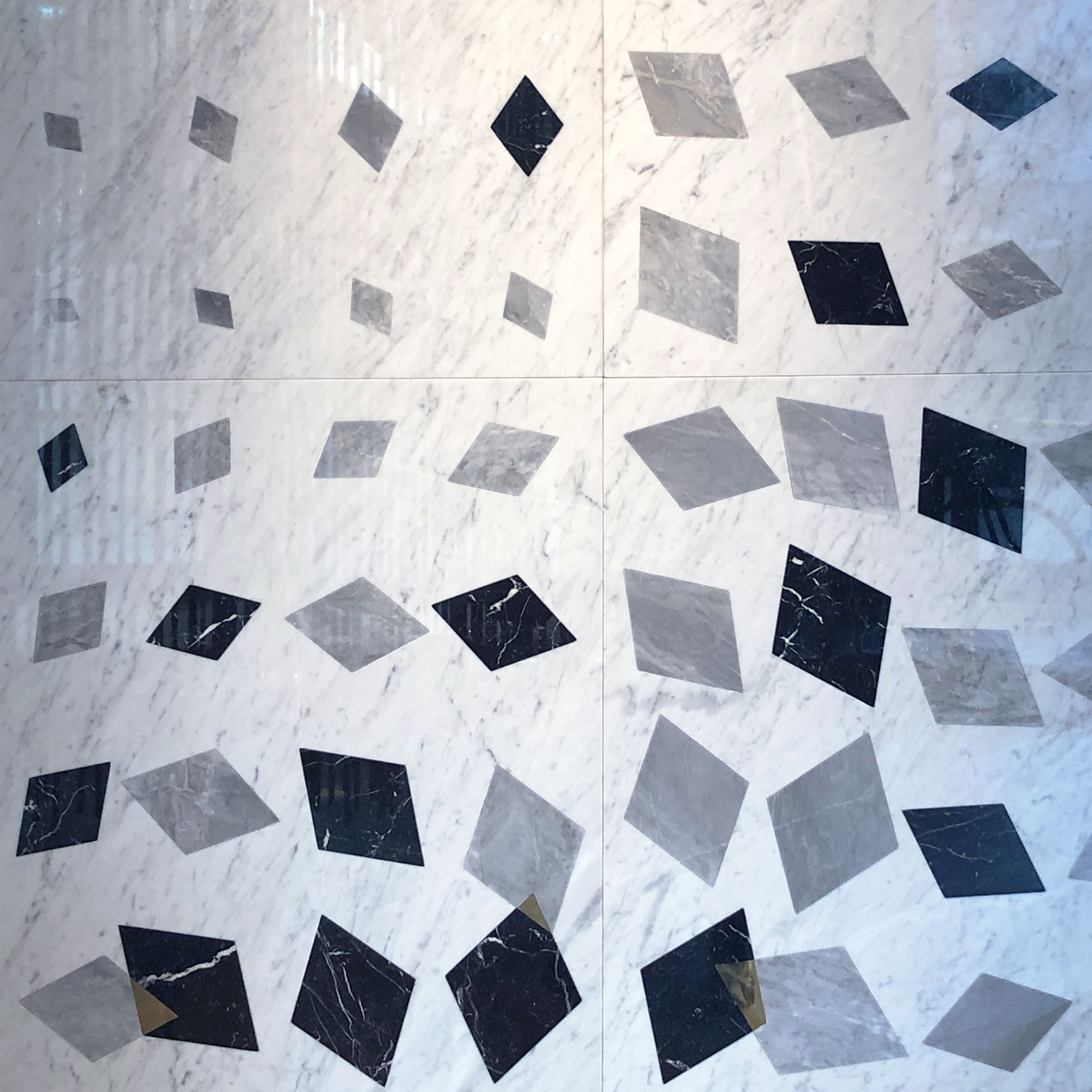 Falling Diamonds - The traditional marble inlaying technique of 'intarsio' is combined here with a computer-generated pattern. Starting from a single diamond shape, an algorithm is used to represent the fall of the stone blocks in the quarry. The shapes multiply, rotate and merge into each other as they fall. During the fall, where black and grey marble merge, they change into brass expressing the entropy growth generated by the encounter. This Inlay technique can be applied to different stones, please request more information.   | Matter of Stuff