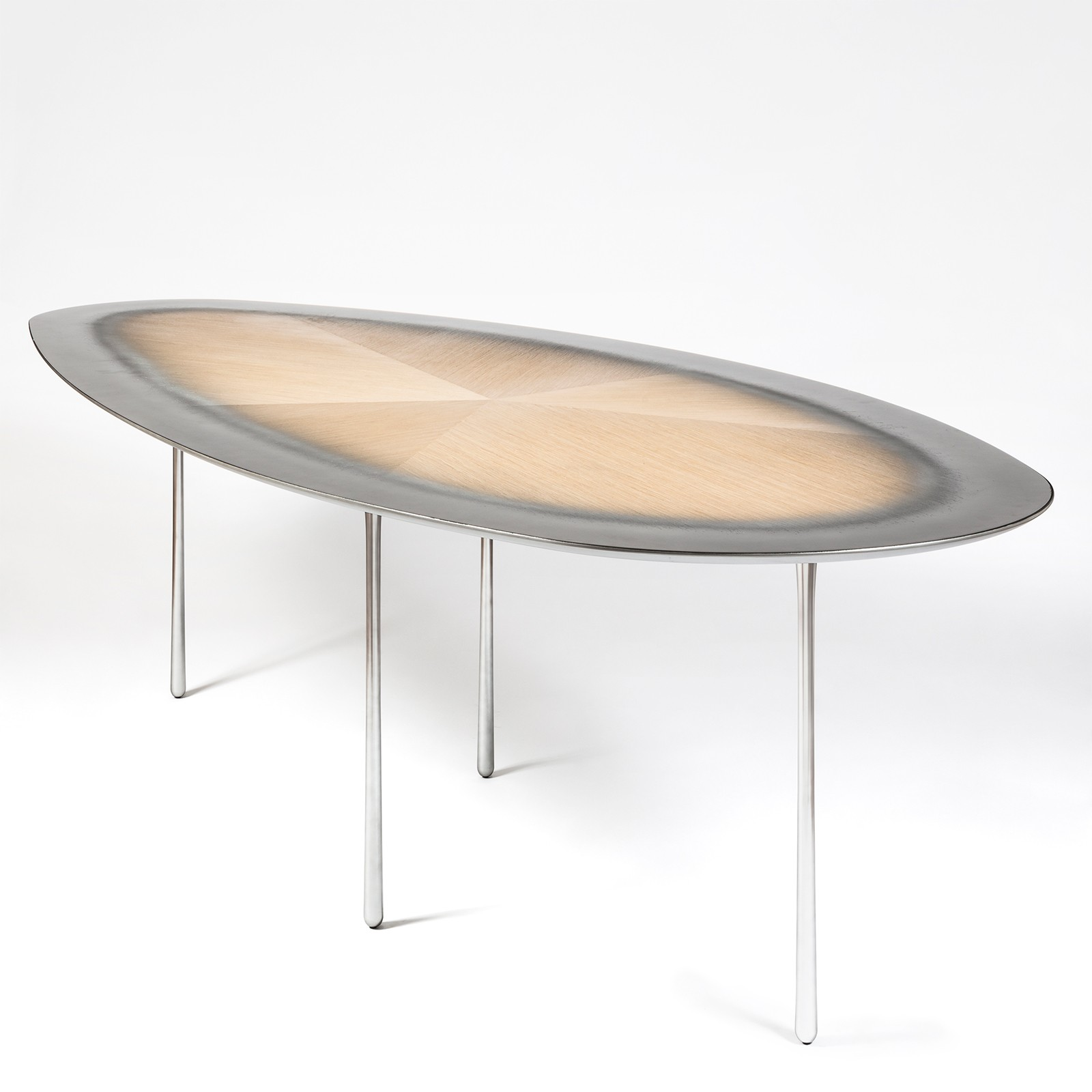 Echo Oval Table - The echo table pushes the material limits of metal and wood to imagine an intangible reality. The grain of wood tells its history, and by using a technique of exposing the hardwood (winter season) and embedded metal into the lines of the softwood (summer season), each growth creates an elusive boundary between the two materials. The objectivity further enhanced by the lightness and thinness in the profile of both materials. Beauty and inspiration are found all around us. The table legs reference the shape generated by the spilling of water. The variation in the shapes of the table top resembles that of stones organically formed by sea current. Enacting the activity and motion which would happen around a table. The colours allude to the subtle shades of a sunrise, created in three types of metal: aluminium, copper, and brass. Developed and produced during the Matter of Stuff Designer Residency program in Montalcino. | Matter of Stuff