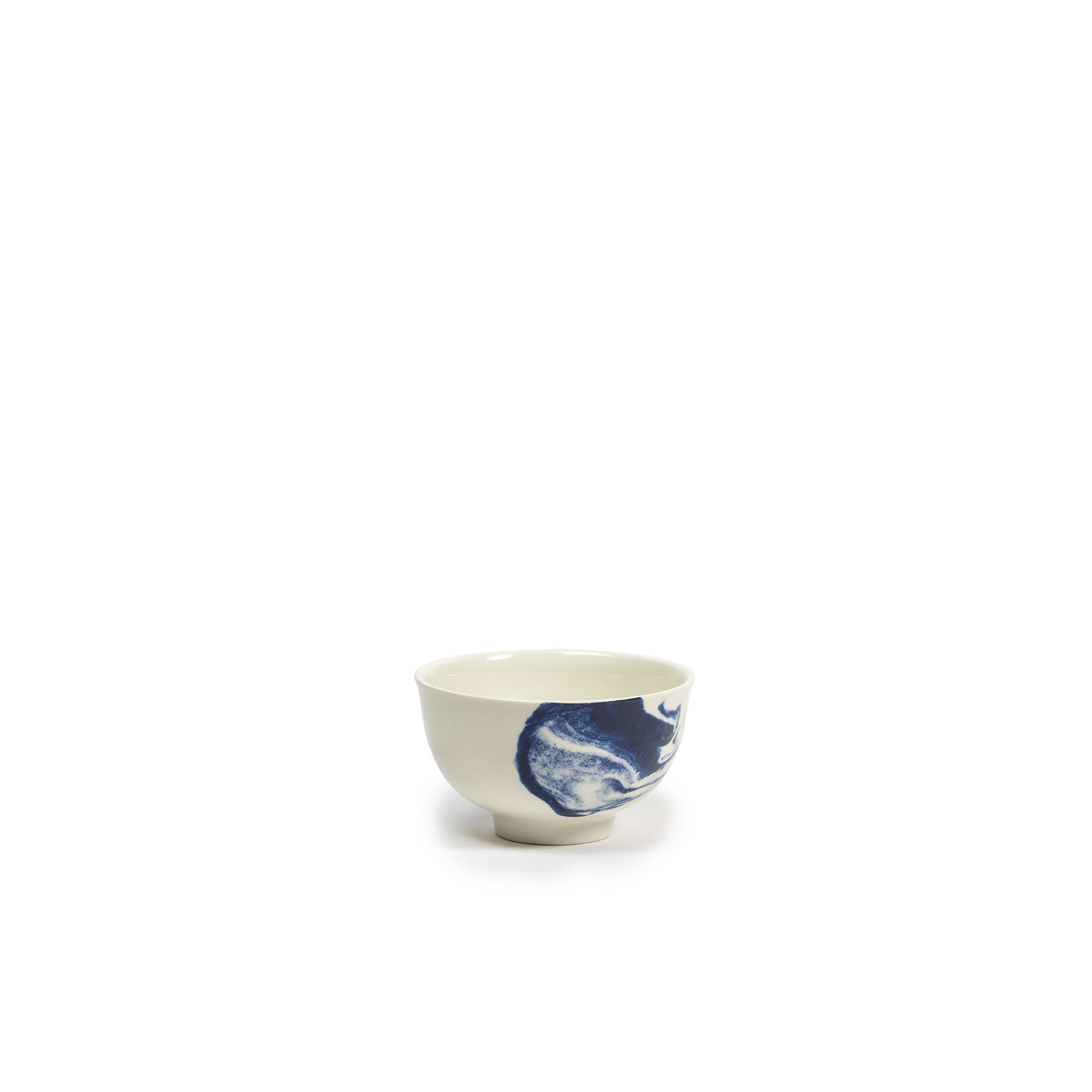 Indigo Storm Handleless Cup - Faye Toogood's range of ceramic designs for 1882 Ltd. celebrates the serendipitous beauty of natural imperfections. Indigo Storm, a new interpretation of traditional creamware forms, draws upon the chance patterns created when pigment added to the slip coating does not fully blend. The whorls and eddies resulting from these experiments, like meteorological formations in miniature, make up the collection's central motifs, appearing on pieces including plates, bowls and cups. Representing a streamlined take on our ceramic heritage, the fine earthenware employs the familiar tones of English Delftware: cream offset with a rich, deep blue. Dishwasher and Microwave safe.  | Matter of Stuff