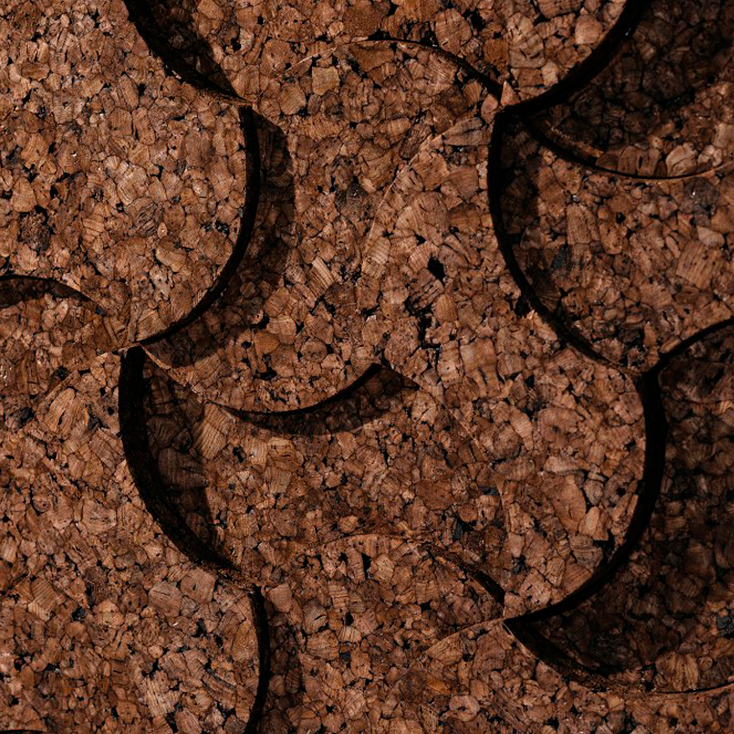 Corkarc Cork Tiles - From a triangular grid to an organic panel. The same element with different thicknesses generates an irregular topography. A great example of simplicity: simple forms that generate complex structures. Easily assembled and with strong aesthetics, it is also a perfect solution for acoustic insulation.  Exploring the symbiosis between low-tech material and high-tech processes. The 100% natural and sustainable expanded cork agglomerate is transformed through generative design algorithms and advanced digital fabrication processes, expressing a new formal aesthetics. This creative and disruptive system not only optimizes cork's thermal and acoustic properties but also adds artistic value to traditional walls. | Matter of Stuff