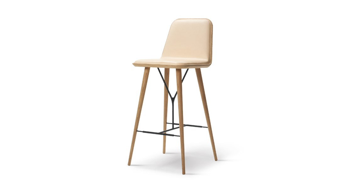 Spine Wood Base Stool Seat Upholstered - Spine is the fusion of Fredericia's craft traditions and Space Copenhagen's dynamic visual language that uses both classic motifs and unorthodox details. Spine Barstool is a high dining chair ideal for public space use. Spine signals a dynamic design language driven by strong lines balanced by subtle curves. Contrasts that merge into a singular, balanced entity. Solid and graphic yet soft and organic.   The design is anchored in Nordic tradition but with a sophisticated, modern twist that gives it a striking, fresh aesthetic.   The Spine series has expanded since its initial launch to encompass a variety of products and a growing number of variants, found in deluxe restaurants, bars, hotels and exclusive retail shops worldwide.   Adding a touch of tension and dimension is the interplay between the upholstery and the base, available in either wood or metal. Spine in wood is classic and luxurious, exuding a certain strength of character. Whereas the sleekness of the metal base signals a look that's more modern and light. The upholstery is inspired by techniques that were developed at our Fredericia workshop for Børge Mogensen's exclusive 1960's leather series.   With its graceful appearance, Spine is all about contrasting elements that culminate in a cohesive concept that's inviting wherever you place it.   Matter of Stuff
