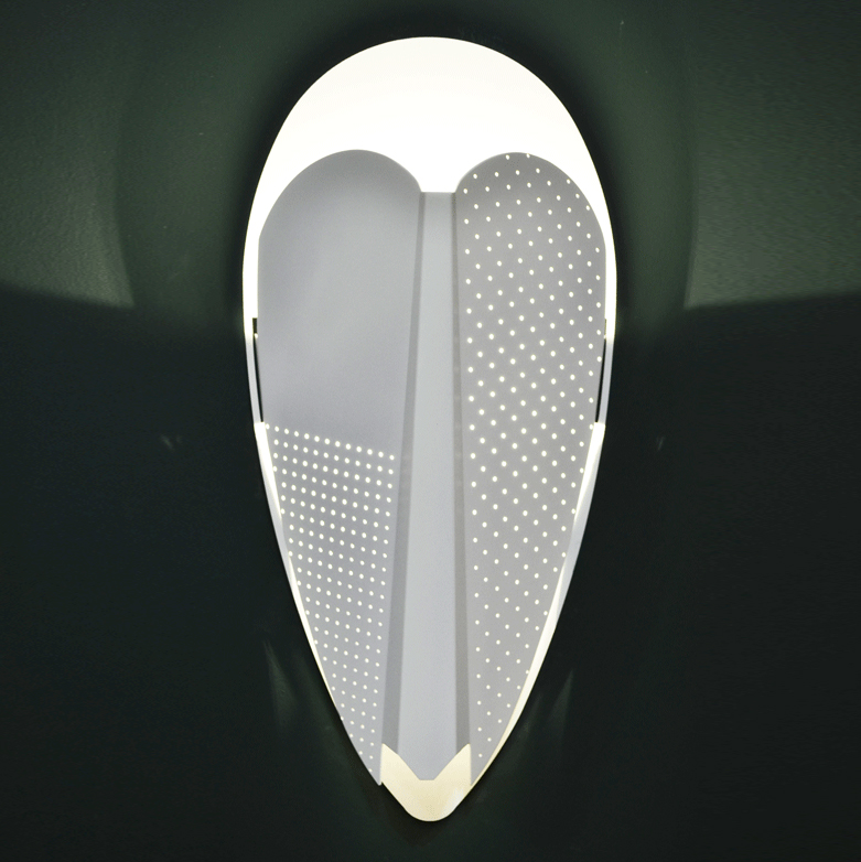 Sorcier Wall Light - <p>Sorcier is a wall light inspired by the ritual Ngil masks of the Fang tribe in Gabon. The light appears through the perforations in the mask and shines upward in a graphic and gentle way. More than a light, Sorcier is a sculpture. It changes personality depending on the combination of colours, textures and perforations patterns.</p>  | Matter of Stuff