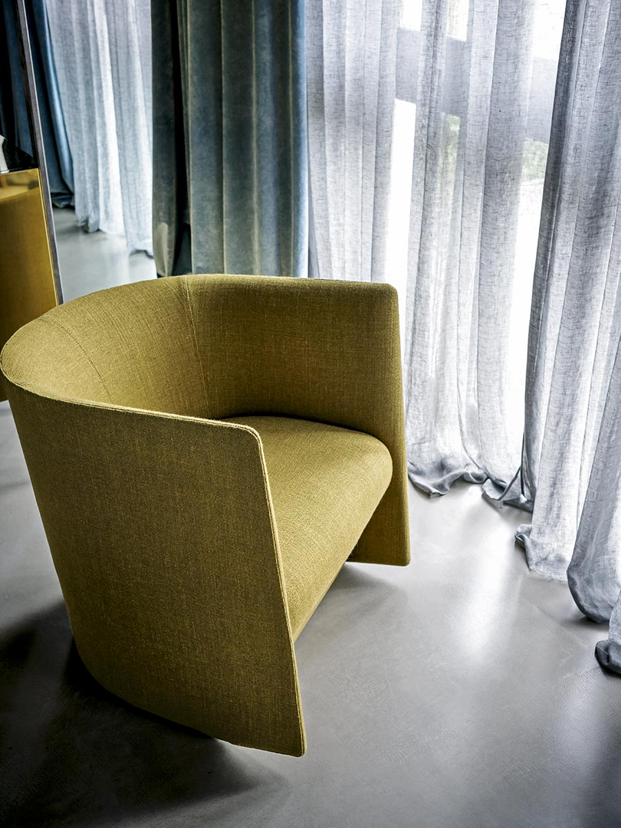 Pisa Lounge Armchair - Essentially designed for public spaces, offices or hotels, Pisa is an upholstered armchair with compact dimensions, suitable for tight spaces but without excluding aesthetic and comfort.‎ Its minimal shapes embrace the body, creating an intimate feeling.‎ Its geometric shape, with the sloping backrest and a cut profile, creates a strong personality despite restrained measures.‎