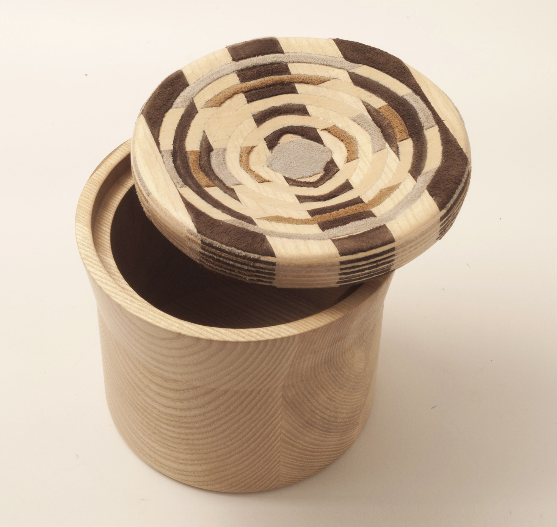 Cad Weaving Jar - <p>CAD weaving is a new material that brings a twist to traditional weaving techniques. It is made by identical pieces of leather and veneer that glued together in a crisscross manner to form a block. The block is then programmed in 3D computer software to find the right pattern and shape and cut in a CNC machine to create the curved surface, revealing a different pattern in each cut. The use of the new semi fabric material on the lid of the wooden jars takes inspiration from classic kitchen jars with patchwork fabric covers.</p>    Matter of Stuff