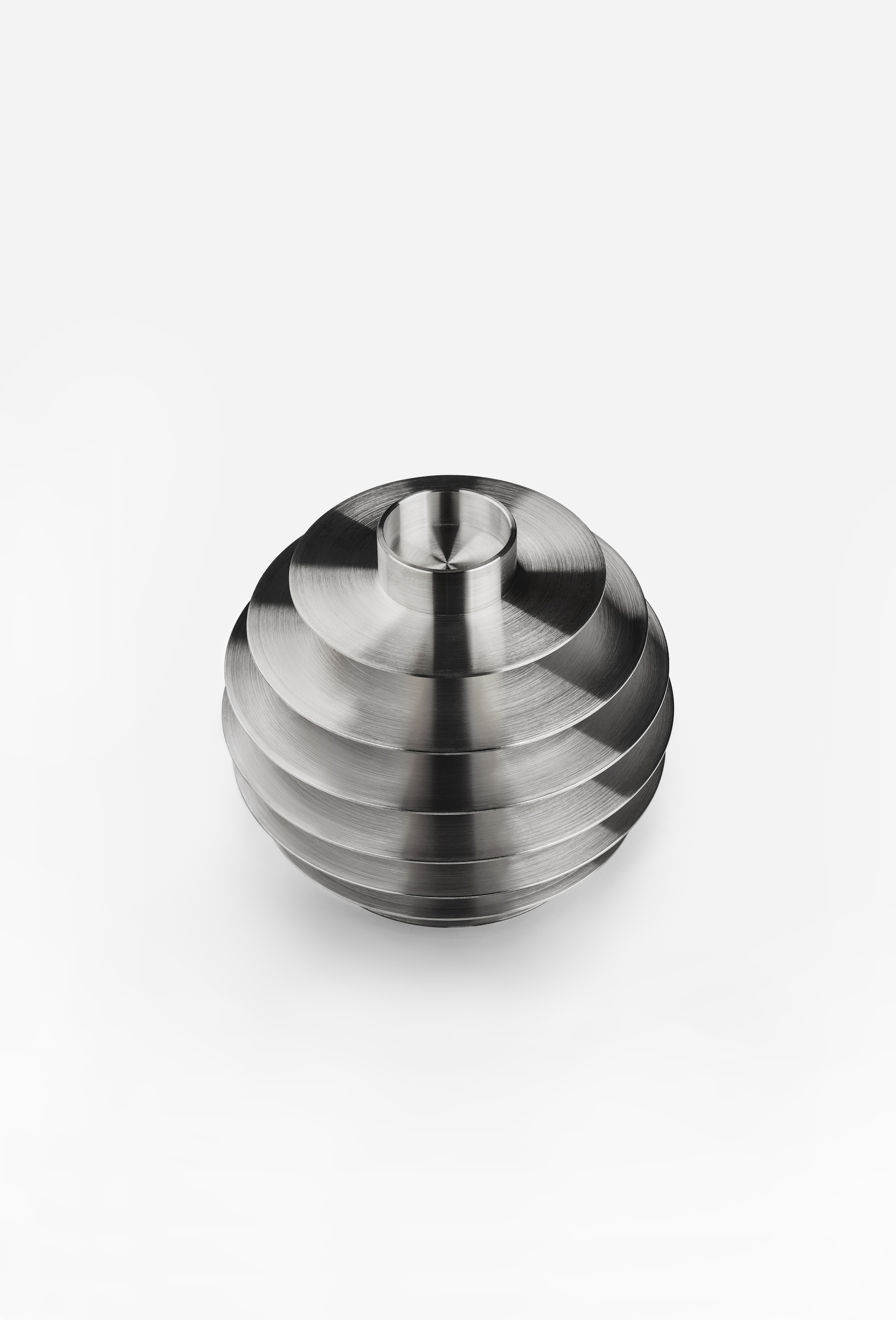 """Modern ORB Candle Holders Set CS2 Stainless Steel - ORB is a set of seven metal candle holders stacked on top of one another to form a modern spherical sculpture. Designed to be functional, each candle holder has two sides to hold long and tealight candles. The collection comes in solid brass and stainless steel making it look charming in any interior setting as a series of seven candle holders or as a single sculpture.  """"I think the universe is pure geometry - basically, a beautiful shape twisting around and dancing over space-time."""" - A. G. Lisi.  The name of the collection, the shape of the whole sculpture and the number candle holders are all inspired by the mystifying universe. Featured by immense and bizarre nature, it has always attracted people at all times. A celestial sphere, characterized by the ideal circular shape, is also manifested in the company name — NOOM — that is semantically associated with the reverse side of the Moon. 