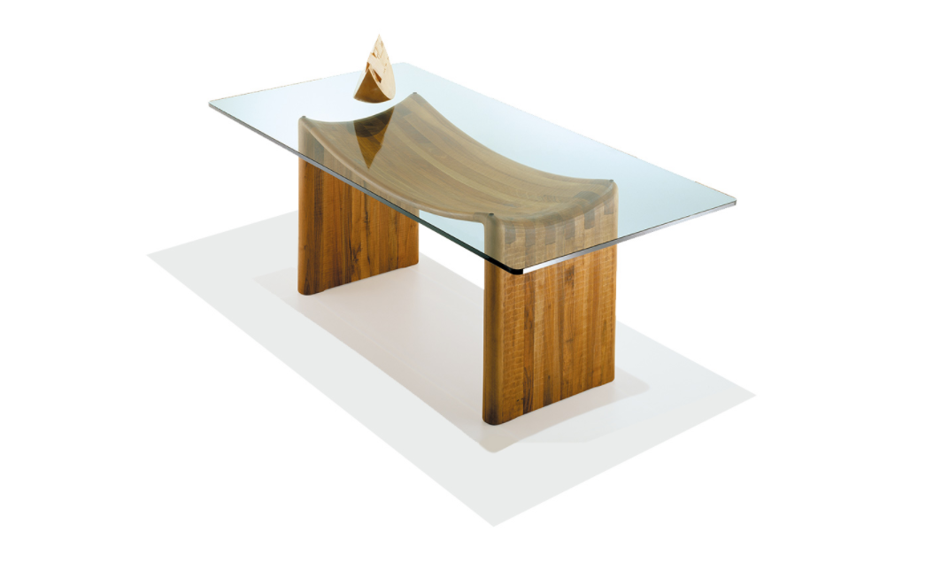 """Velabro Dining Table - <p>Velabro is a table made as a single block using wood with vertical grain. It is manually finished on all sides using a gouge. The top is made of 2 cm thick extra-clear glass. The entire manufacturing and finishing process is carried out manually in our workshop. The wood used for this piece is Juglans Regia – common Italian walnut; not dried but """"raw"""". This wood belongs to the Latin tradition of furniture-making and features an extremely compact fibre which can, however, be worked without too much difficulty; it is therefore highly suitable for household items. Over time the wood hardens and becomes extremely resistant, and oxidises slightly to take on a progressively warmer amber colour. The soft curve of the support gives the Velabro table an original and elegant appearance.<br /> Customised and made with European cherry, Slavonian oak, maple.</p>  