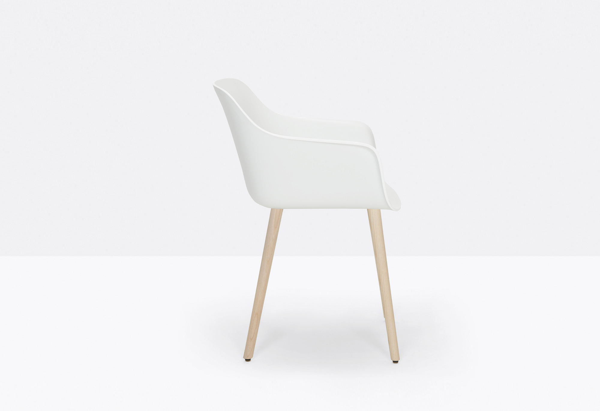 Babila XL Armchair - Babila XL fits harmoniously within a collection poised between tradition and innovation. An armchair with a polypropylene shell stands out for the large dimension of its seat and armrests. Solid ash wood legs.