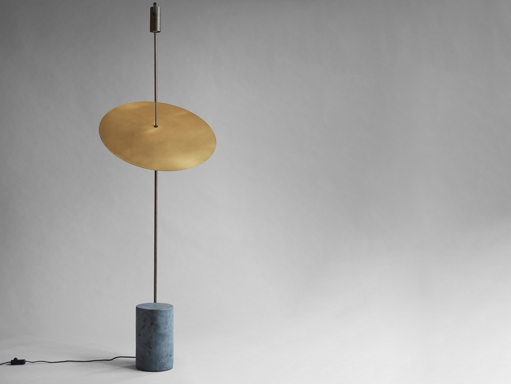 The Moon Floor Lamp - The Moon is a minimalistic floor lamp inspired by minimal arts and industrial sculptures. The lamp is a carefully constructed geometry, where each component is perfectly weighted in relation to each other.  The lamp has two light sources placed as compositional fix points along an oxidized brass arm. A large circular lampshade is hanging from the lamp arm as a floating reflector in the space. The reflector lampshade of brushed brass is illuminated on both sides and creates a warm and soft light setting. The lamp is mounted to the cylindrical base of unpolished black marble in order to stabilize the structure.  | Matter of Stuff