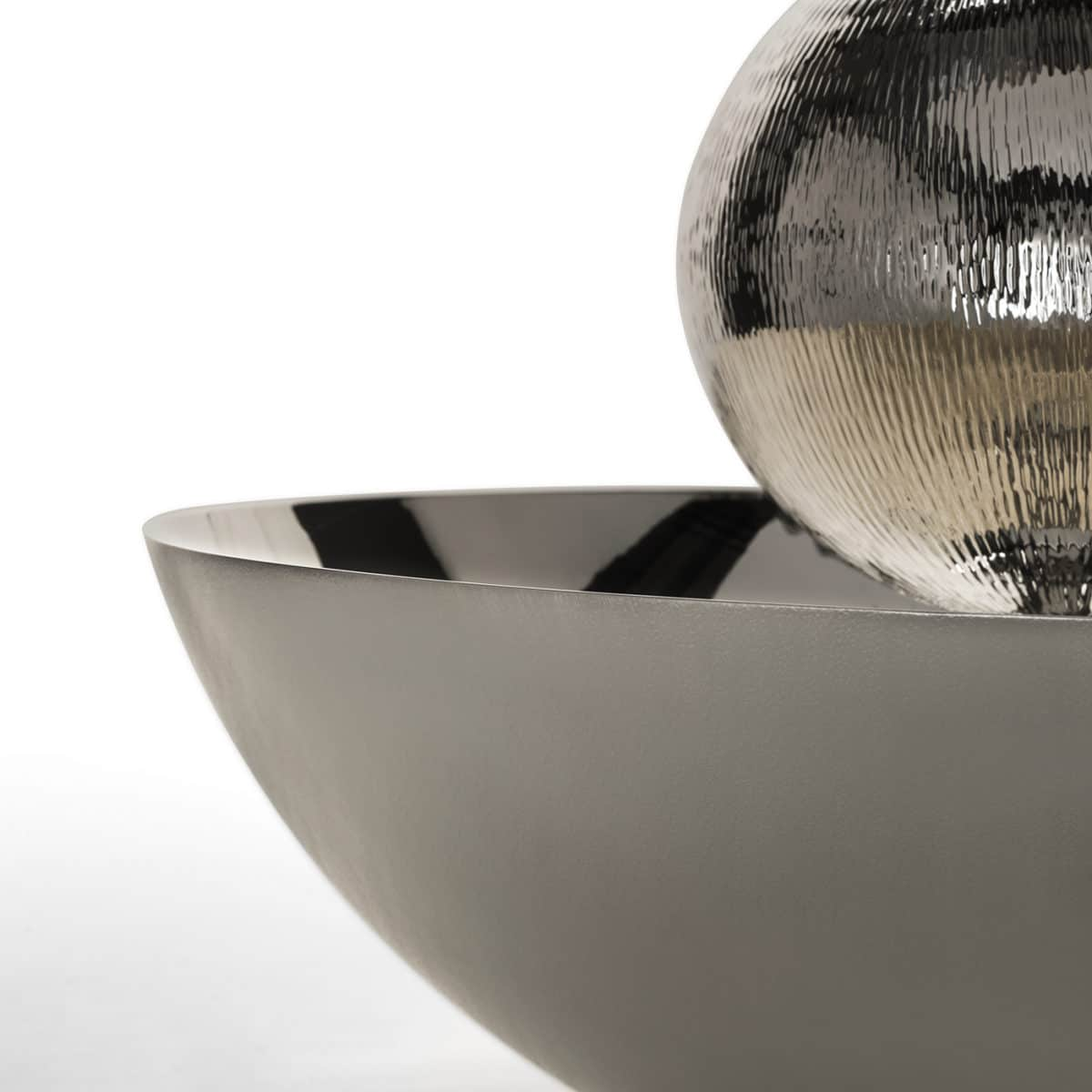 Balliamo Sul Mondo Centerpiece - This unique centerpiece is part of a numbered series and will be sure to make a statement in any contemporary or modern home, thanks to its geometric silhouette and special gleam. Made of silver-plated metal with a varnish finish, its sinuous and smooth surface reflects the surrounding light in a unique way. Its circular base supports a sphere at its center that seems to float in midair. Evoking the cycle of life and the perpetuity of time, this piece will be a standout addition to an entryway or a dining room.