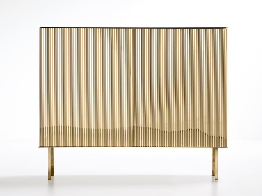 Elizabeth Sideboard - Like a ballerina on her toes, Elizabeth gracefully unfurls her luminous dress, as if made of pleated fabric.‎ The characteristic folds add movement to the metal sheet along the surface of the cabinet, transforming each reflection into light.‎ In an interplay of airiness and tension, elasticity and rigour, the metal vibrates with the rhythm of its pleats.‎ Available in steel, brass or copper, Elizabeth gives shape to a new way of imagining unambiguously feminine metal furniture.‎