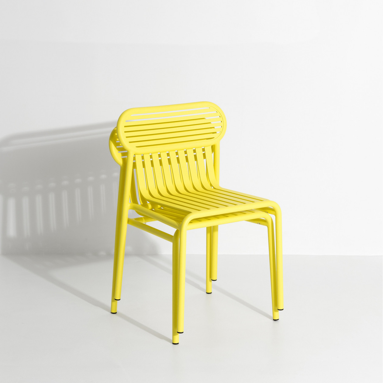 Week-End Chair - The WEEK-END collection is a full range of outdoor furniture. Designed with practicality in mind, all of the seats are stackable. The Week-End collection is a complete range of outdoor furniture. The oval and circular shape drawn by the backrests makes them a graphic statement. The impact of the horizontal and vertical slats, so similar to stripes, highlights the full and empty spaces, asserting the identity of the collection.  | Matter of Stuff