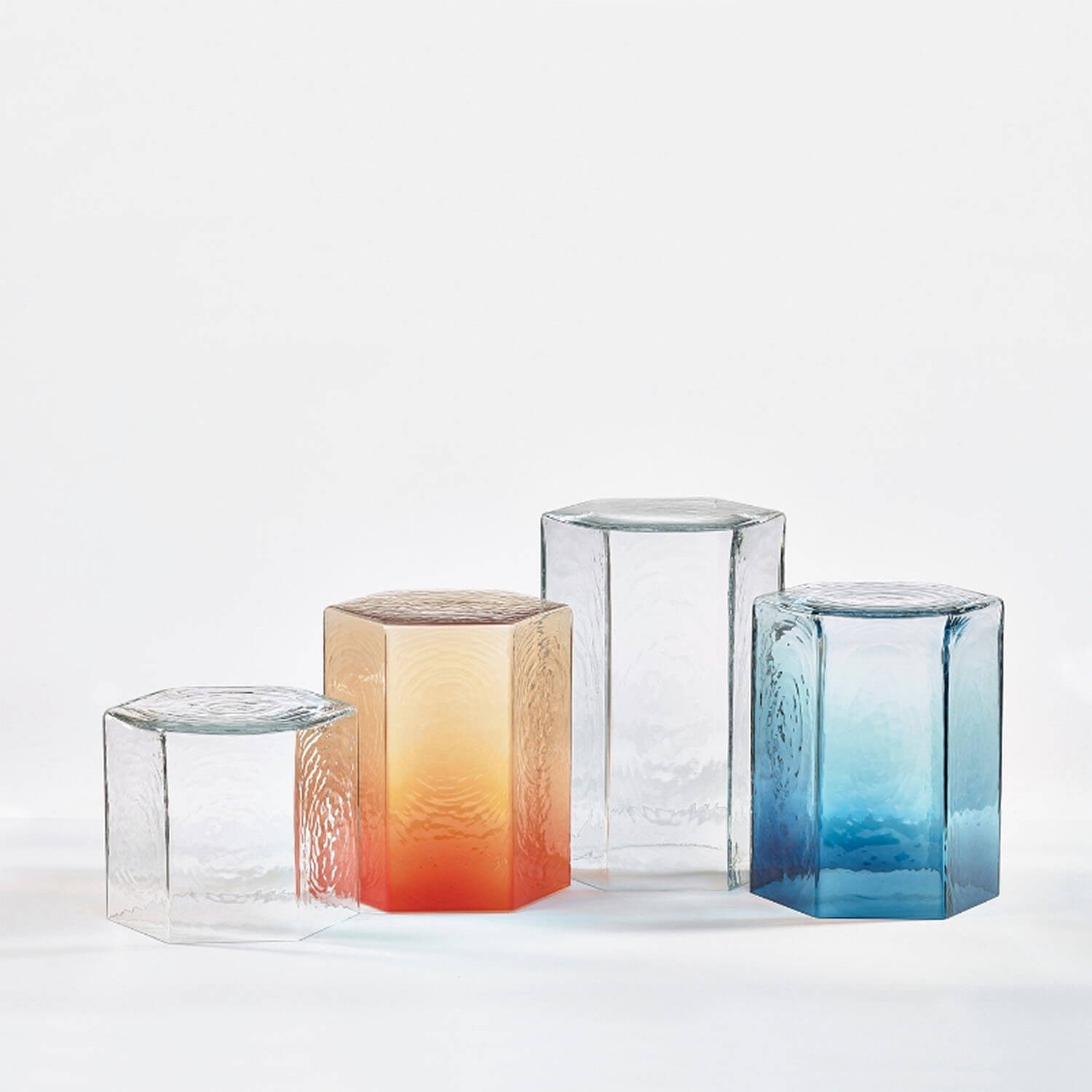 Hex Large Clear Table - <p>A fascinating play of light and shadow.<br /> These unique tables are inspired by the perfect hexagonal structure of quartz crystal, the very material that gives birth to glass. Its liquid texture is captured on the rippled surface in a fascinating play of light and shadow. Colours pay homage to quartz varieties in nature. Enjoy them as a single side-table or create brilliant crystal islands by combining their hexagonal shapes. The hex tables are mouth-blown thus the intensity of colour may slightly vary.</p>  | Matter of Stuff