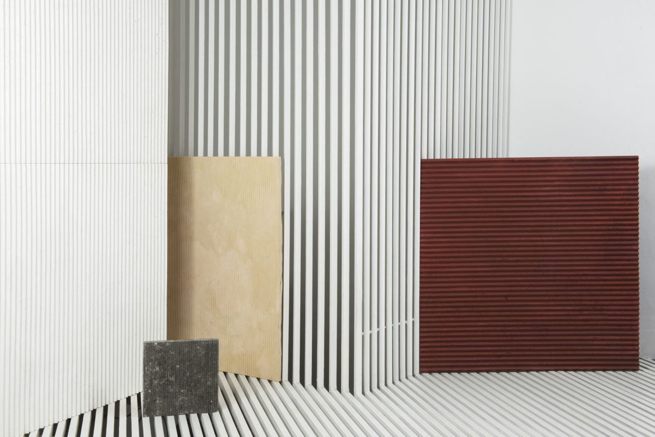 """White Medium Ruts - Obtained by stretching the impasto first by hand and then with CNC machining, Ruts alternates between flat portions, reminiscent of stone, to rectangular sections to create a succession with a solid and fortunate rhythm. The """"cadence"""" of its grooves can be more or less dense, continuous or interrupted, but in each of its versions and in all the different colors, Ruts reveals, thanks to the intervention of the machine, the material uniqueness of paper pulp. They are indeed hard, mechanized cuts that speak of the very fiber of the paper as it pushes toward new dynamic and formal borders. 