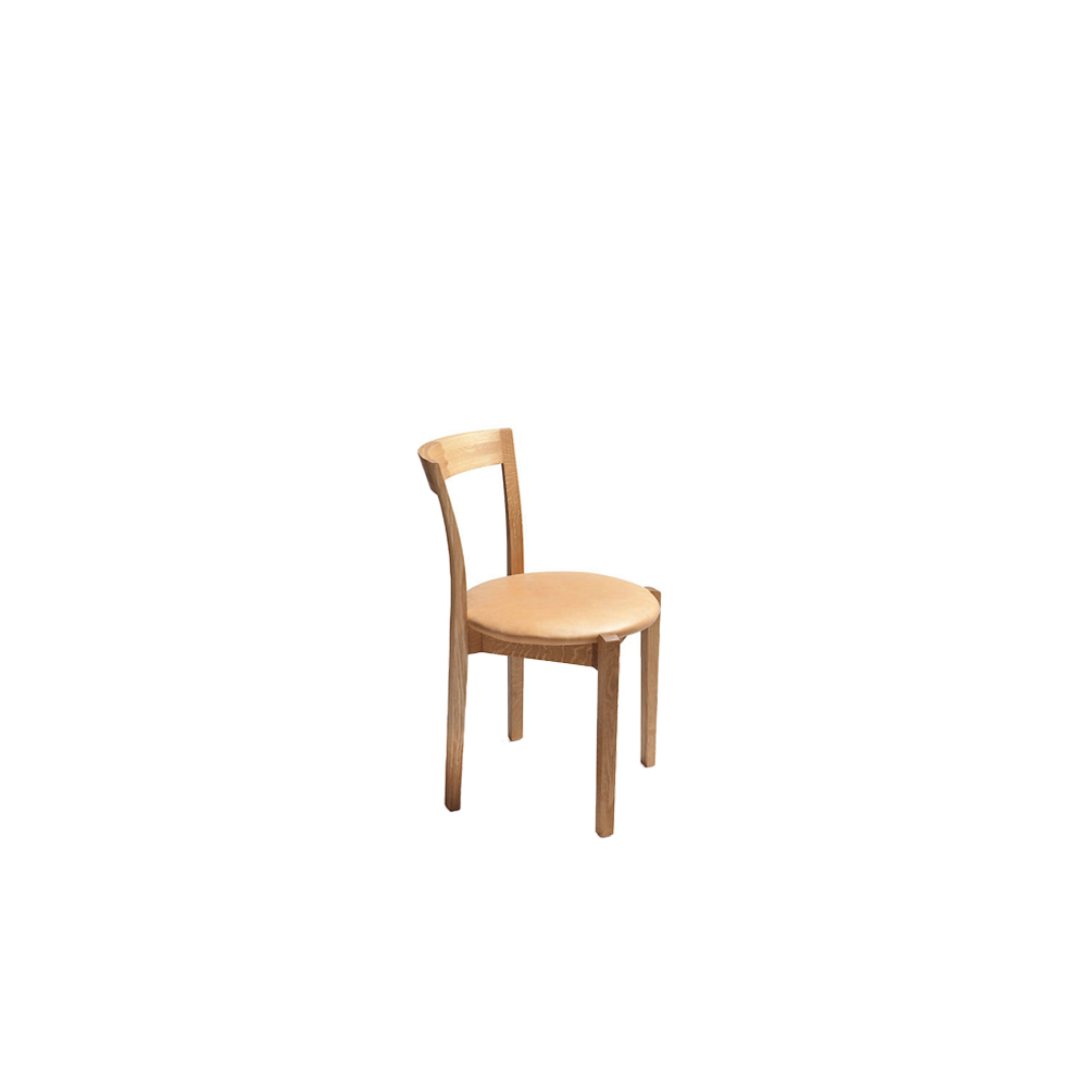 Classic Chair - The Classic chair by Rudi Merz has an elegant spirit and graceful design. The backrest is adorned with skilfully crafted wooden joints that function both as constructive and aesthetic elements. The Classic chair is available in oiled oak, ash or black-stained ash, and its round seat is upholstered.  Part of the Café collection, the Classic chair stacks spirally, is comfortable to sit and lightweight to move. The chair's timeless look suits a range of different styles from historic interiors to contemporary settings. It also serves as a dining chair in homes and restaurants alike. Nikari's wooden furniture is treated with natural surface treatment materials, such as natural wood oil mixture, water-based lacquers and waxes. Nikari also uses naturally tanned leather as their standard leather option.   For upholstery options and wood species, please refer to the upholstery/wood species catalogue. Customer's own fabric and COM colour are available for an individual price upon request. | Matter of Stuff