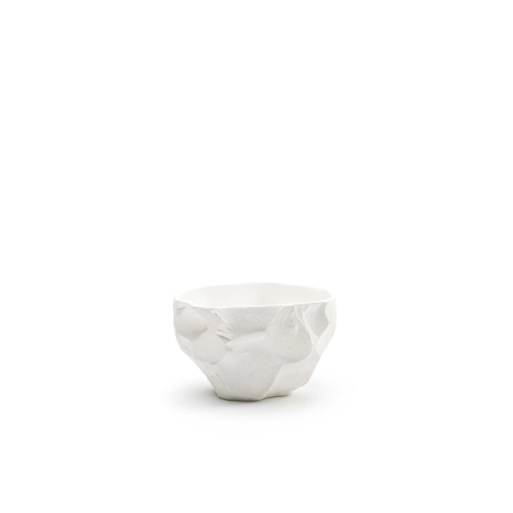 Crockery White Small Bowl - A collection of fine bone china tableware slip-cast from plaster models carved by hand, with glazed interior for functionality and raw exterior reflecting the modest surface texture of the plaster original. The process of slip-casting begins with the creation of a three-dimensional model of the design known as a master by a professional model-maker, from which the production mould is cast. Crockery bypasses this process by placing the responsibility of both designer and model-maker in the hands of Max Lamb. Using the tools of a stone mason Max chips and carves a solid block of plaster to make a series of tableware, the design of each formed quite simply out of their own making. Microwave and dishwasher safe.  | Matter of Stuff