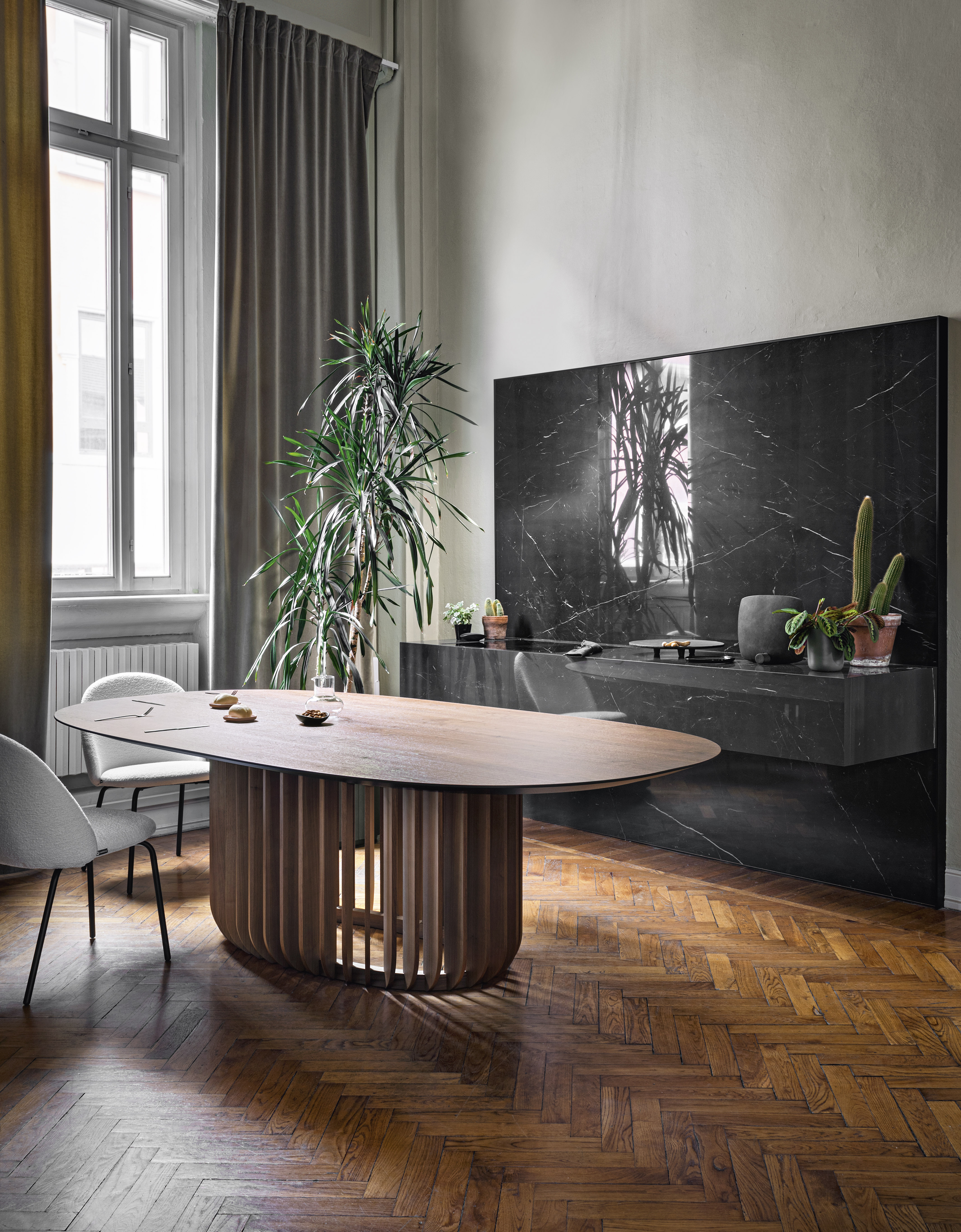 Juice Oval Table - Juice is a monumental table with a meditative air. Its essence lies in the base, where the long wooden legs attach to a ring, encircling it. Juice, a table developed around the balance between filled and empty spaces, creates a sensation of perfect calmness. The table comes with wood or ceramic top. The wooden base is available in natural oak, canaletto walnut or black ash. | Matter of Stuff