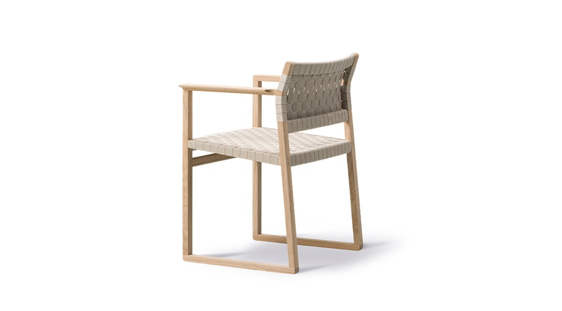 BM62 Armchair Linen Webbing - Børge Mogensen brings us back to nature with the choice of cane wicker or linen webbing coupled with a solid wood frame. In a slender design involving only what's crucial to the construction. By carefully calibrating the angle of the back rest, it's a simple yet striking dining chair that's comfortable before, during and after dinner.