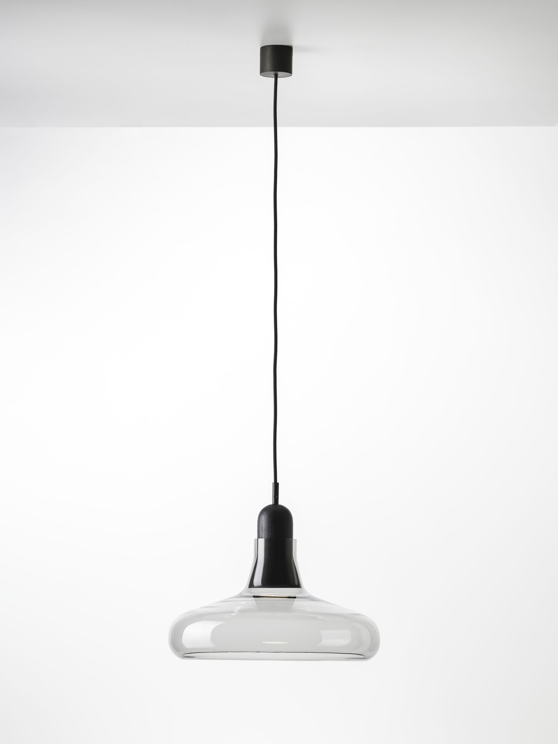Shadow Pendant Lamp - <p>The Shadows collection is a take on the famed, timeless lights found in French ateliers, and its typology pays tribute to that legacy. The combination of handblown glass, handcrafted wood, and classic shaping has given rise to a light of ageless elegance. The collection comprises four different suspension lights, as striking alone as they are in sets, characterized by a handblown glass shade set upon on a handcrafted wooden body. The clean contours and finish are accentuated by the concealed light source. The Shadows collection is special not only for its wide spectrum of glass colour options, surface finishes, and types of wood but also because the lights can be combined into sets according to customer requirements. They are intended for interiors and, thanks to multiple combination possibilities, are well suited to a broad range of installations. Both the Shadows and Shadows XL collections have special integrated connectors developed by Brokis to facilitate installation and cleaning. The craftsmanship applied in production follows in the centuries-old tradition and experience of master glassmakers. The precision crafting of hand-blown glass instills distinctive, enduring character and outstanding quality in all Brokis products. The glass shades are formed from multiple layers of molten glass, each of which is scrutinized by the master glassmaker prior to being blown into the mold. Up to 70% of the resulting quality is achieved in this stage of production. No less attention to detail is paid in handcrafting the wooden elements of the light. Each piece is individually processed by the artisan in a series of strictly observed production stages. We take special care in selecting quality fine wood and ecologically friendly materials to treat it with.</p>  | Matter of Stuff