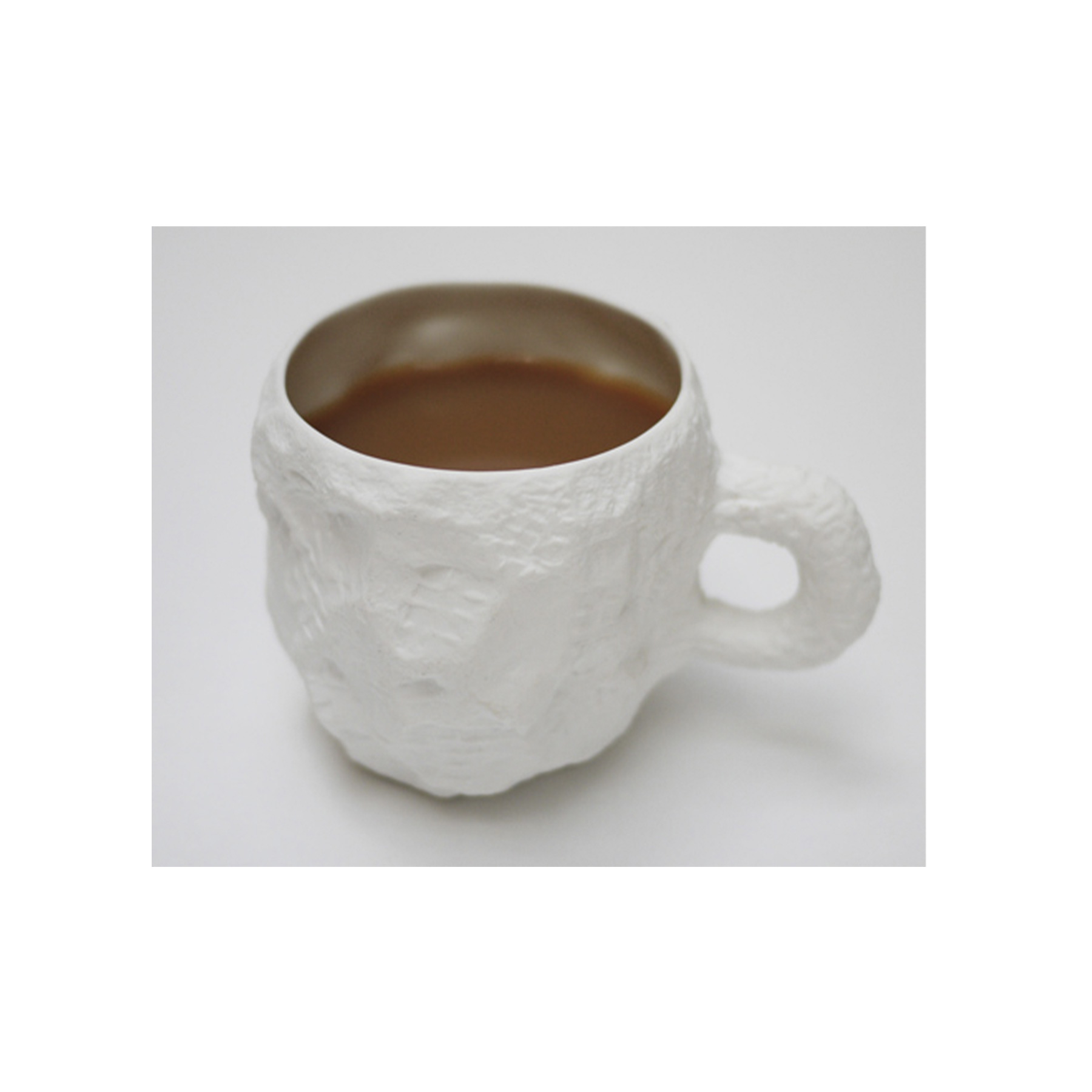 Crockery White Mug - <p>A collection of fine bone china tableware slip-cast from plaster models carved by hand, with glazed interior for functionality and raw exterior reflecting the modest surface texture of the plaster original. The process of slip-casting begins with the creation of a three-dimensional model of the design known as a master by a professional model-maker, from which the production mould is cast. Crockery bypasses this process by placing the responsibility of both designer and model-maker in the hands of Max Lamb. Using the tools of a stonemason Max chips and carves a solid block of plaster to make a series of tableware, the design of each formed quite simply out of their own making. Microwave and dishwasher safe.</p>    Matter of Stuff