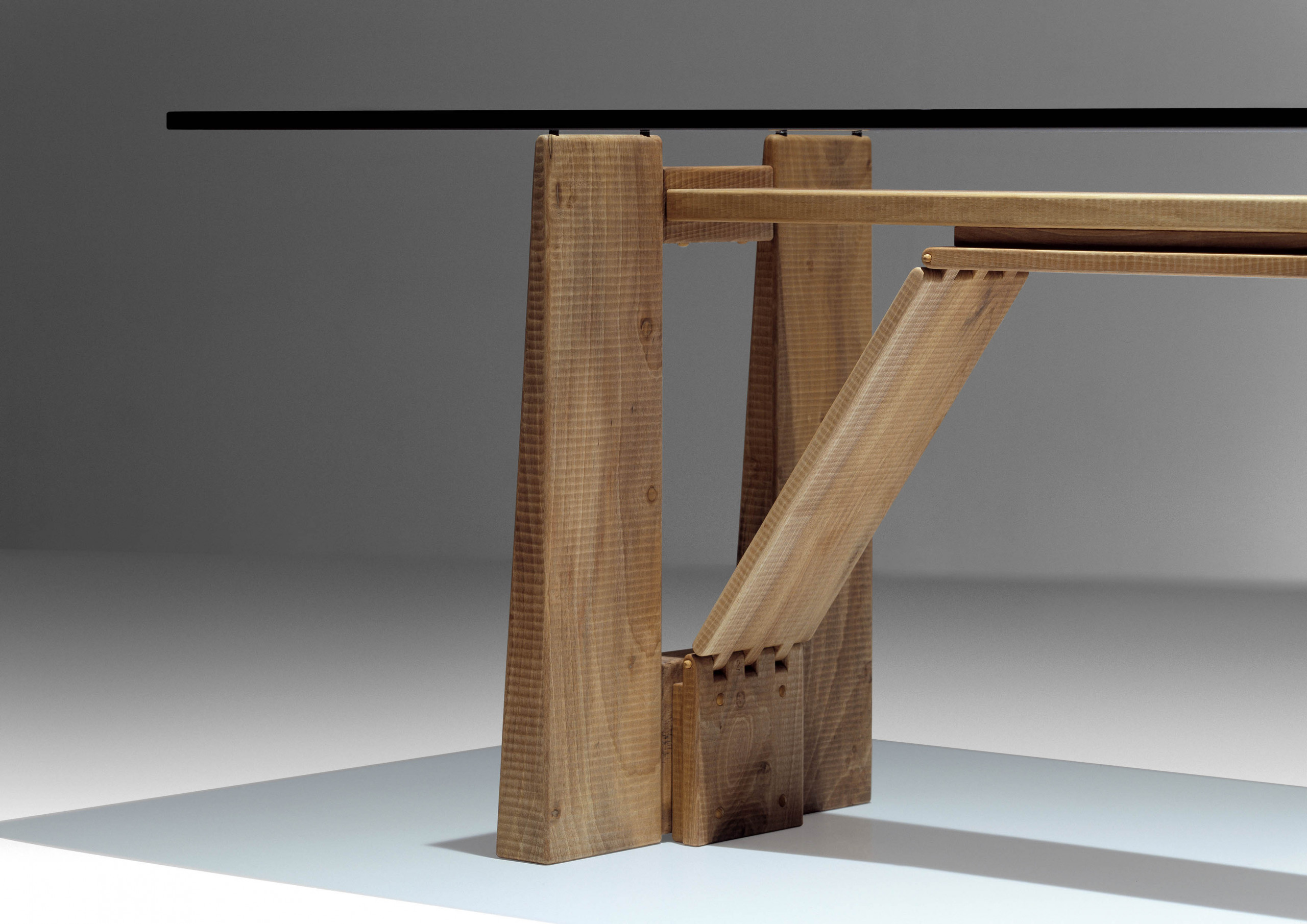 "Perugino Dining Table - <p>Perugino is a table made by assembling interlocking slats of solid wood, manually finished on all sides by planing. The pyramid-shaped load-bearing elements are stabilised by lightweight trusses, which support the whole structure with precise joints. The top is made of 2 cm thick extra-clear glass. The entire manufacturing and finishing process is carried out manually in our workshop. The wood used for this piece is Juglans Regia -common Italian walnut; not dried but ""raw"". This wood belongs to the Latin tradition of furniture-making and features an extremely compact fibre which can, however, be worked without too much difficulty; it is therefore highly suitable for household items. Over time the wood hardens and becomes extremely resistant, and oxidises slightly to take on a progressively warmer amber colour.<br />