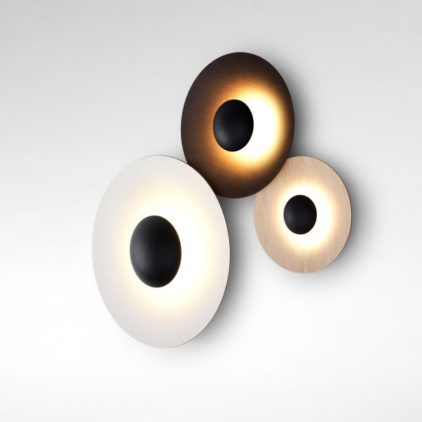 Ginger 20C Wall Light - Wood is a great ally of cozy lighting. It is a material that is hard to mold, a challenge that the Ginger collection neatly resolves. The combination of sheets of wood, paper and resins pressed together under high pressure achieves a laminate that appears almost entirely flat, which discreetly lights up spaces with indirect light.  The Ginger collection has been expanded over time to provide solutions to different lighting needs, and is available in pendant, table, wall, and floor lamp versions. This time, we are adding a new, smaller suspension lamp, a portable table lamp, another version of wall lamp with a movable arm, and three different sizes of flush-mount wall lamps.  This year we present the new version of Ginger in metal, which offers the same reflected, warm, glare-free light that helps to accentuate spaces. This material is applied to some models of the collection with different finishes: brass, black and white outside and brass and white inside. A new, lighter option that's refined, almost like a sculpture. Also new in the Ginger collection is the size of the wall version, with a 20-centimeter diameter and which, along with the rest of the collection, can be installed as a set to yield a static, almost artistic object, circles where the metal finish is smooth to the touch and pleasing to the eyes. With these two highly diverse materials –wood and metal– the Ginger turns into a versatile collection, rounding out the circle and offering a lamp for every lighting and decorating need.  This wall lamp can be combined with other similar wall lamps to create a composition. Please refer to images to see possible combinations.  | Matter of Stuff