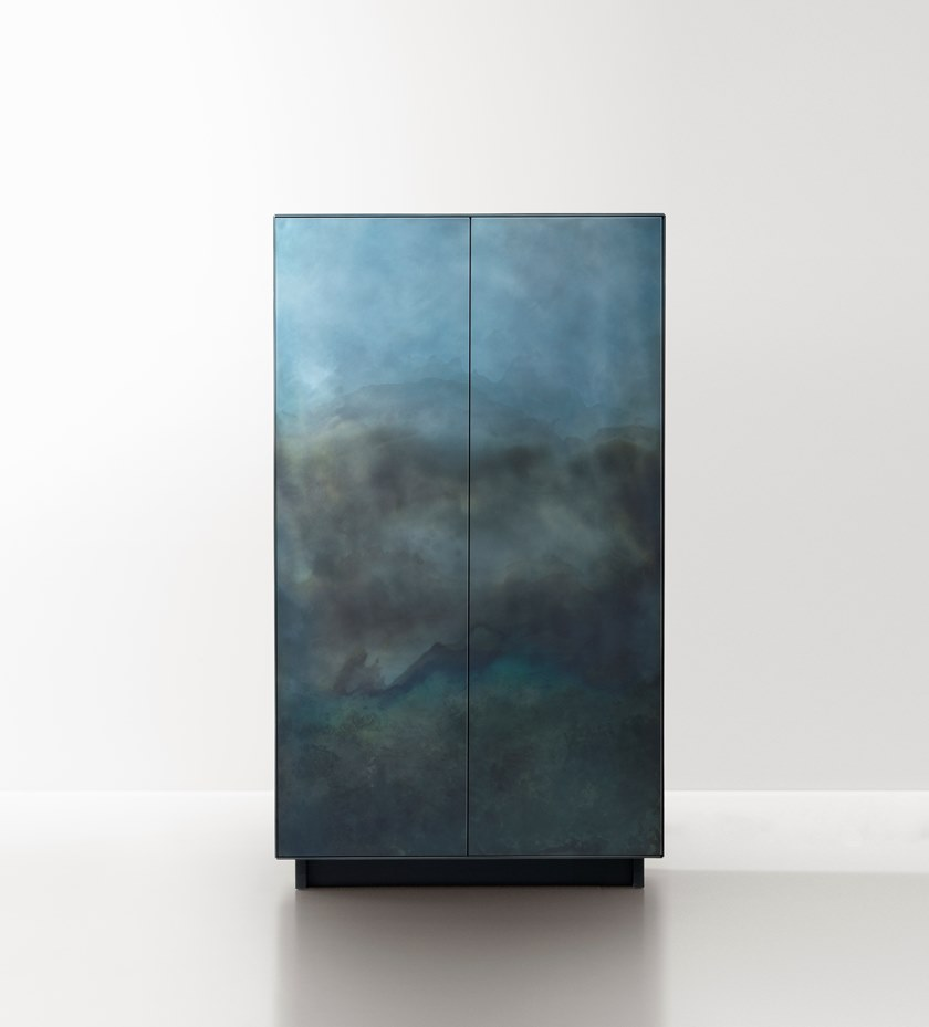 Marea Cabinet - The traces of time are drawn one on top of another, infused into the changing skin of the rigorous metal forms that define these cabinets and chests.‎ Like the tide (marea in Italian) leaves its mark, wave after wave, even here the hand of the craftsman has left its sign, oxidation after oxidation, creating a painterly effect that resembles water's erosion of the material.‎ Somewhere between design object and work of art, each piece in the collection, composed of a chest of drawers, low credenza and cabinet, is unique thanks to an entirely hand-crafted finish that transforms the metal surface into a delicate watercolour.‎
