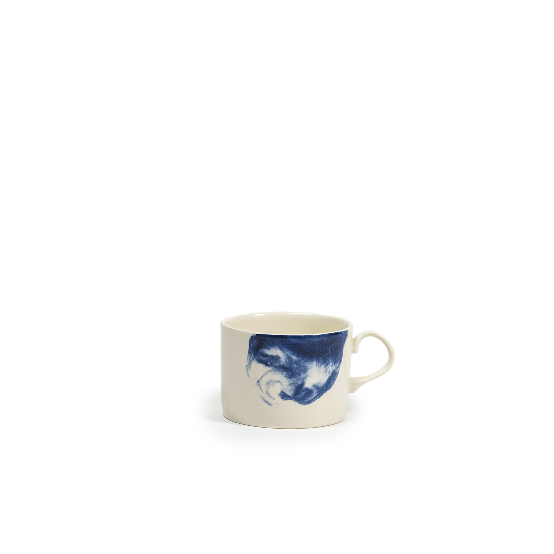 Indigo Storm Mug - Faye Toogood's range of ceramic designs for 1882 Ltd. celebrates the serendipitous beauty of natural imperfections. Indigo Storm, a new interpretation of traditional creamware forms, draws upon the chance patterns created when pigment added to the slip coating does not fully blend. The whorls and eddies resulting from these experiments, like meteorological formations in miniature, make up the collection's central motifs, appearing on pieces including plates, bowls and cups. Representing a streamlined take on our ceramic heritage, the fine earthenware employs the familiar tones of English Delftware: cream offset with a rich, deep blue. Dishwasher and Microwave safe.