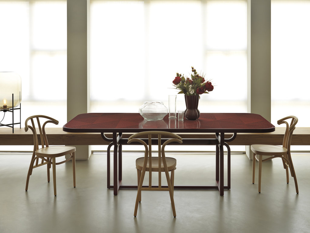 Caryllon Dining Table - The retro allure of this piece is conveyed by the square section of the structure, in striking contrast with the rich decorative treatment of its surface, the round corners at the top, and curved base. The top is adorned with a handcrafted straw inlay inspired by straw marquetry and tinted in vivid red, as in the Art Deco style. A homage to Michael Thonet, this solid wood table is available in two different heights.  | Matter of Stuff