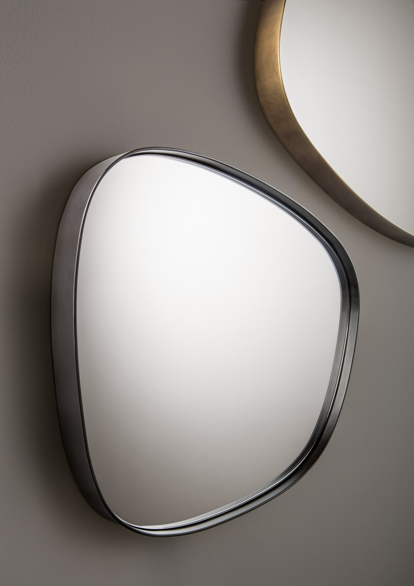 Syro Mirror - The Syro Mirror echoes the organic silhouettes of the entire Syro collection, translating them into mirrored surfaces that, surrounded by thick iron and brass frames, mimic the natural outlines of petals. In a mix of chromatic effects obtained from various metal treatments, these multifaceted shapes can be arranged as desired, on their own or one next to another. The organic nature of the collection is thus amplified, revealing the multiple ways they can be combined on the wall, to surprisingly dramatic results.  Supplied with fixingsystem. Also sold individually.  | Matter of Stuff