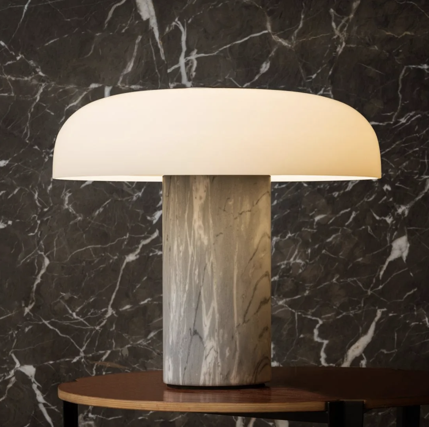 "Tropico Table Lamp - The ""shape of light"" is the central theme of this project by Gabriele and Oscar Buratti, which began with the Equatore family of lamps, presented in 2017 and now expanded to include other finishes, and continues with the new Meridiano and Tropico. Forms of glass and metal that collect, contain and diffuse light in space. Passing between opaline, coloured and transparent layers, emphasised by the refined curves and the magic of blown glass, the light is free to create surprising and fascinating effects, patterns and moods. Tropico is a spherical cap of opaque opaline glass, flattened and fixed by a large mirrored metal boss. The family comprises wall/ceiling and table versions, both available in three different sizes.