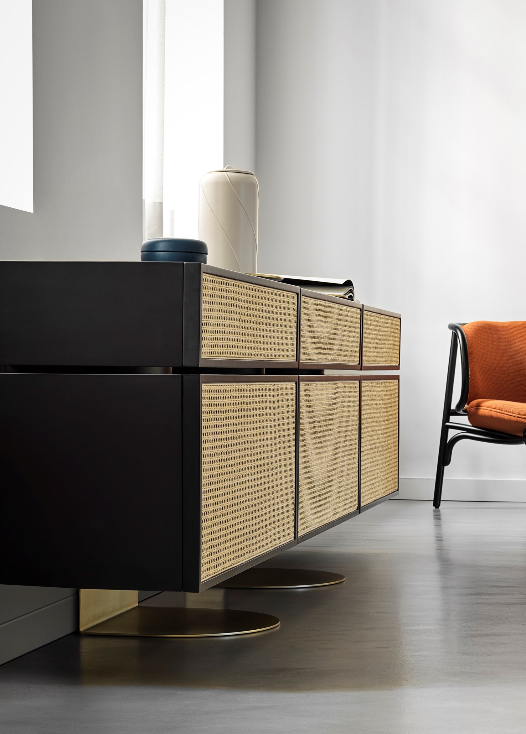 NYNY Sideboard - Distinctively asserting its modernity, Gebrüder Thonet Vienna has adopted its archetypes, bent-wood and woven cane, to design NYNY, a piece of furniture with a strong emotional dimension capable of imposing itself in space as the absolute protagonist of the scene. With its versatile personality, this multifaceted design by storagemilano expresses an interdependence of design, architecture and art that draws inspiration from both the typical post-modernist styles and the graphic playfulness of the 1980s while creating an irregular development of perspective accentuated by the intense colour scheme. The reference to architecture is also reflected in the name NYNY as New York, New York. The play of volumes of NYNY is, in fact, a tribute to the New Museum of Contemporary Art in Nolita, whose building expresses the archetypal forms of the Babylonian ziggurat. With a totemic spirit, NYNY is defined in the asymmetrical superimposition of geometric volumes suspended with the support of the wall-mounted metal structure. Each volume corresponds to a specific function: below, two drawers, one high and one low; above, two compartments with doors. The lower one can also be used as a desk. NYNY is a family of storage units, all characterised by the strength of the creative language typical of storagemilano, a balanced encounter between creativity as a designer, and the design language of architects. | Matter of Stuff