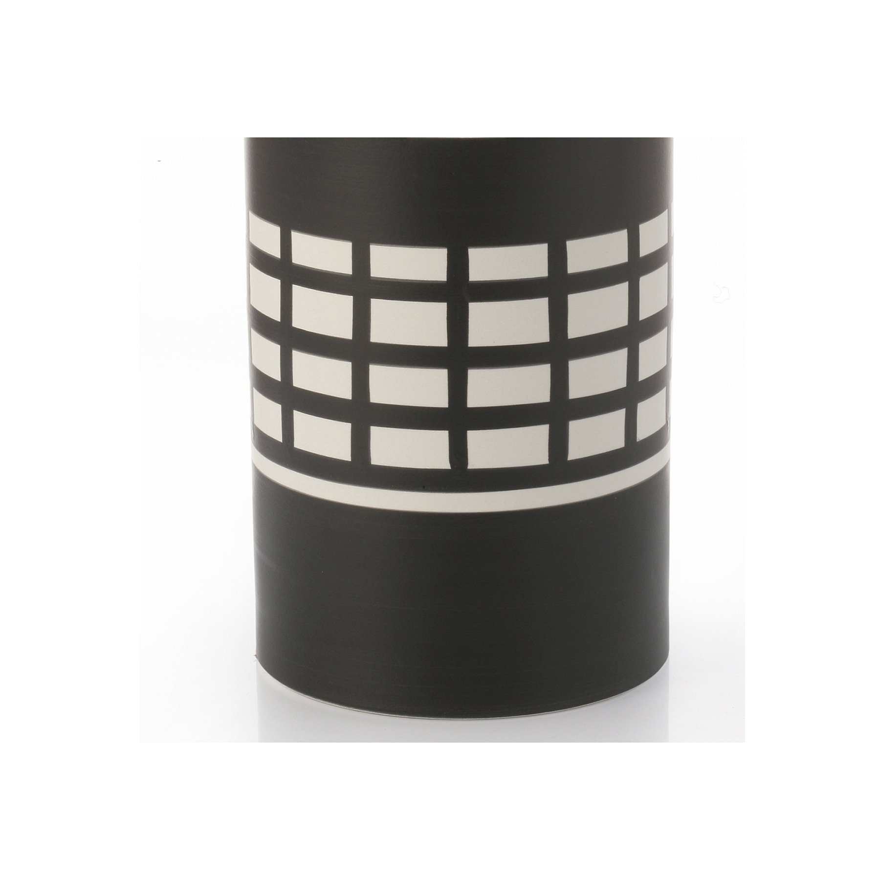 Vaso Rocchetto - Vase B&W series. Hand-turned in white clay. Two-tone matt black and white glaze. This vase's simple shape is complemented by its geometric decoration that features striking motifs in black on the white background of the cylindrical shape. This piece was designed by renowned architect Ettore Sottsass in 1962. | Matter of Stuff