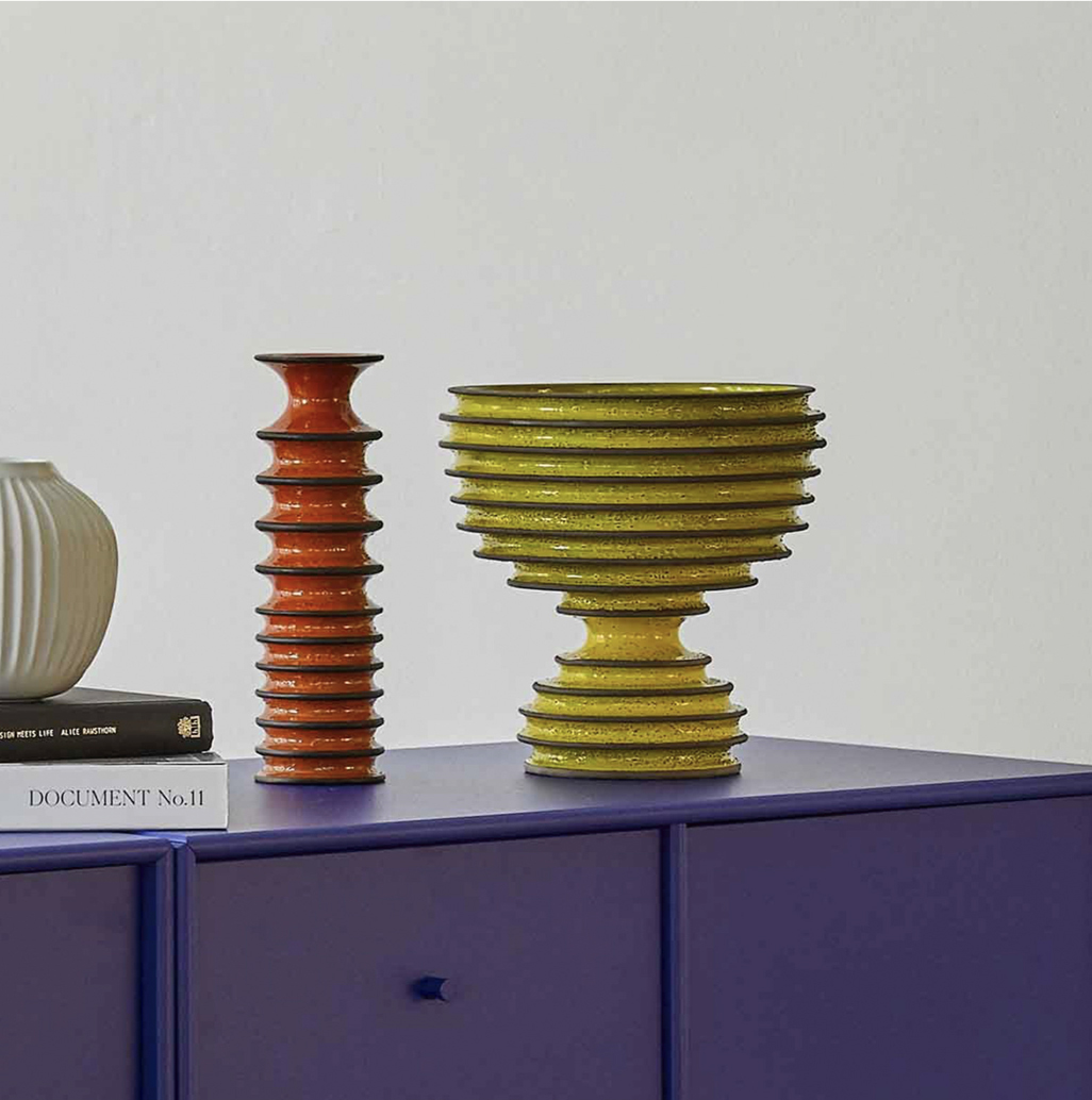 Revolver Orange Vase 1 - This exquisite vase will add an intense dash of colour to any interior thanks to the intense hue of yellow it is enamelled with. The evident, ribbed texture defining its profile results particularly emphasized at the centre with borders accented in brown. Part of the Revolver Collection, the piece was showcased at the prestigious Milan Design Week in 2019. | Matter of Stuff