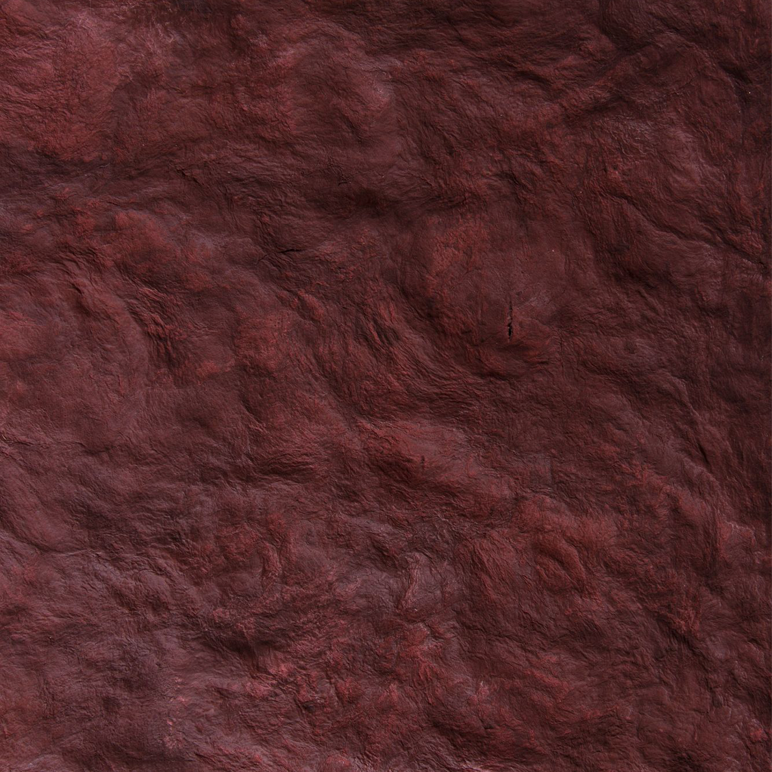 Red Informale - Stretched and hammered by hand, the Informal collection takes shape, generating lunar surfaces, organic and inorganic, almost like a leather with an irregular and unexpected design. Composed of solids and shallows, of pressure and material depressions, serrations and natural curls. Stories of a physicality to be explored by scrolling with hands and eyes along a different path, always in evolution. Among the skins, this is the one with the highest tactile value, all the while maintaining the technical features of impermeability and durability that characterize all of the paper pulp products. | Matter of Stuff
