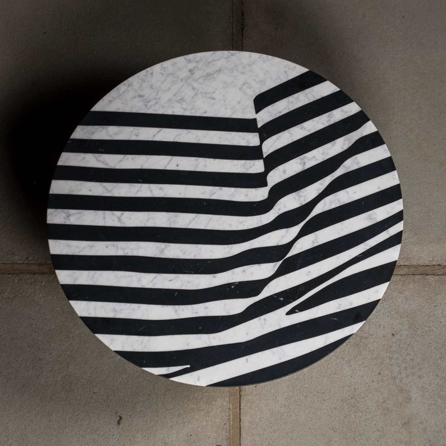 """The Veiled Small Side Table  - <p>The Veiled is a collection of tables and trays made of marble with a graphical pattern inspired by an ancient statue.<br /> It experiments with the dichotomy between a silk and soft looking surface for a hard material like marble.<br /> The effect of light and dark-coloured marble in stripes is both graphic and illusional.<br /> The pattern catches your eye and invites you to touch.<br /> It combines a modern technique and aesthetic with the traditional way of making inlays.<br /> Developed and Produced during the """"Matter of Stuff Designer Residency"""" program in Montalcino, Italy.  Round side table with marble top and marble or metal base.  