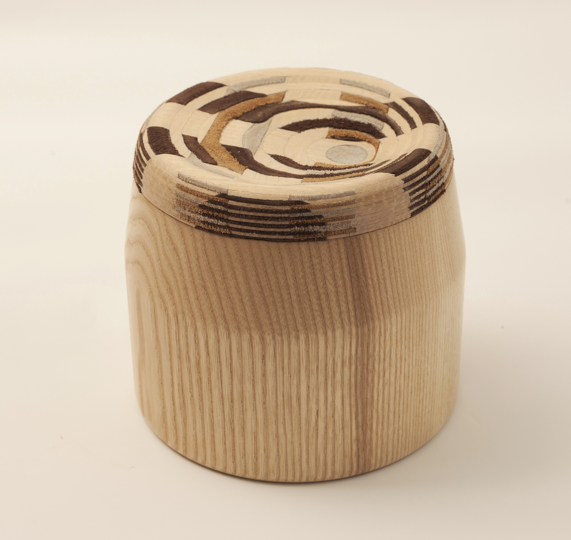 Cad Weaving Jar - <p>CAD weaving is a new material that brings a twist to traditional weaving techniques. It is made by identical pieces of leather and veneer that glued together in a crisscross manner to form a block. The block is then programmed in 3D computer software to find the right pattern and shape and cut in a CNC machine to create the curved surface, revealing a different pattern in each cut. The use of the new semi fabric material on the lid of the wooden jars takes inspiration from classic kitchen jars with patchwork fabric covers.</p>