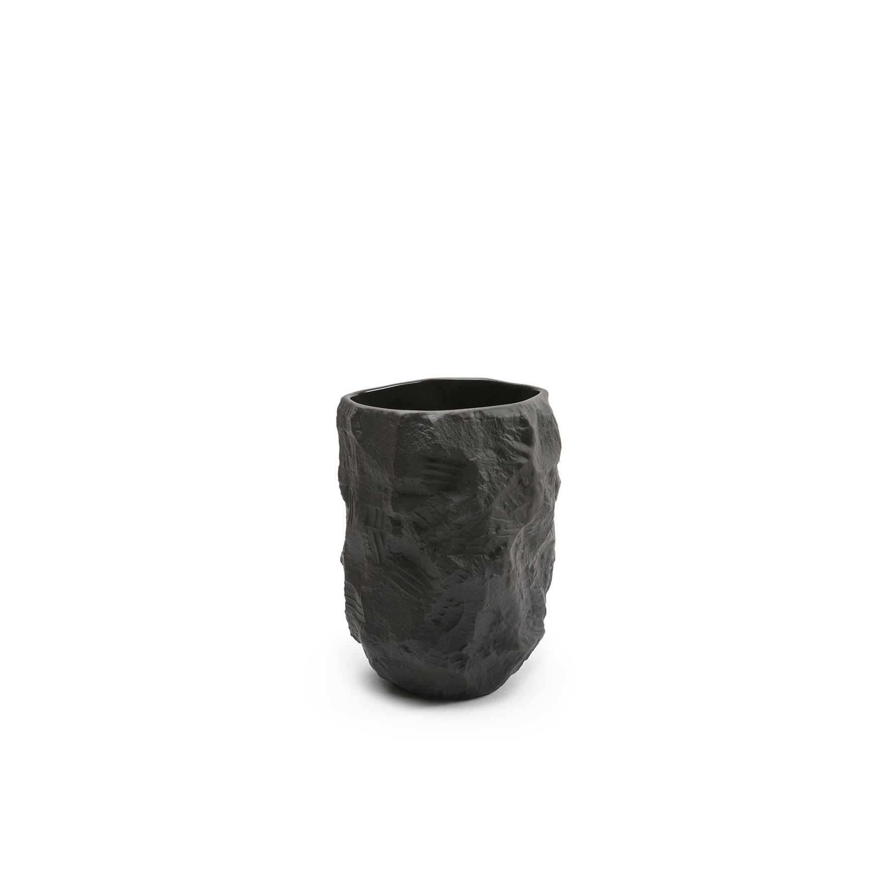Crockery Black Tall Vase - 1882 Ltd.'s interpretation of black basalt, Crockery is a collection of fine bone china tableware slip-cast from plaster models carved by hand, with glazed interior for functionality and raw exterior reflecting the modest surface texture of the plaster original. Using the tools of a stonemason Lamb chips and carves a solid block of plaster to make a series of tableware, the design of each formed quite simply out of their own making.  | Matter of Stuff