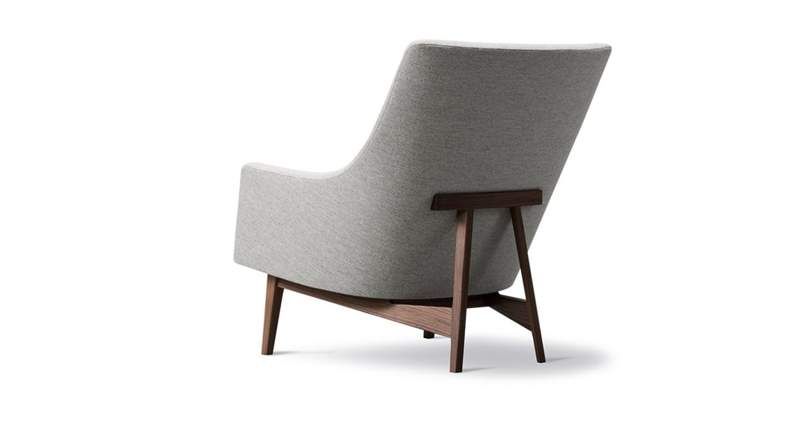 """A Lounge Chair Wood Base - Originally designed by Jens Risom in 1961 the A-Chair is a graceful expression of an elegant, upholstered chair in a timeless design, boasting an A-frame in the back for added support and as signature detail. The curved lines of the two-piece back and loose seat cushion accentuate the comfort and softness of this foam-filled chair with a base available in solid oak, walnut, black lacquered steel or matt chrome.  Jens Risom known for introducing a Scandinavian design sensibility to the American market. There he pursued a successful career designing an array of pieces which stemmed from functionality, imbued with a New York sense of style and savoirfaire. Risom went on to leave a legacy of stunning, streamlined designs.   Echoing his sentiment that """"when sizing up a chair, do it sitting down"""", Risom's design of the A-Chair fuses comfort with a well-tailored sense of class. The A-frame in the back cradles the entire chair, and what began as a functional detail became the signature trait. The slight angle of the back is mirrored in the angles of the arms, adding a sense of equilibrium to the leaned back look. The twopiece back and seat cushion add comfort and are discretely incorporated into the design as graphic elements.   It's graceful, comfort-conscious chair driven by a purpose. Originally conceived in 1961, the A-Chair will always look modern in any milieu, exquisitely executed so lounging becomes a luxury.  