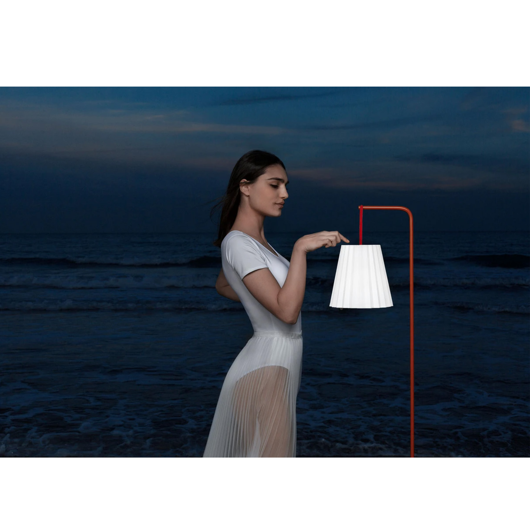 Plisy Portable Lamp with Stand - The Plisy nautical cord handle is available in several colours and can be used to move the lamp from place to place like a lantern or on the wrist. Charge it up at home and take it to the park, to the beach or for a night walk. This lamp is perfect if you do not have light sources in your outdoor area. Use the handle to hang it as a wall lamp or place it on its base as a floor light. Plisy is intended as a portable outdoor lamp, but you can also use it indoors. Use its base to set it near a dining table or reading corner, a hallway area or by the entrance to the house. Use it as an auxiliary table lamp inside the house, when you need to light up your outdoor area or take it with you to a night outing. The lamp base is available as a separate product in thermo-lacquered metal white or red. Please enquire us for further information.  7h Charge/10 h Light. | Matter of Stuff