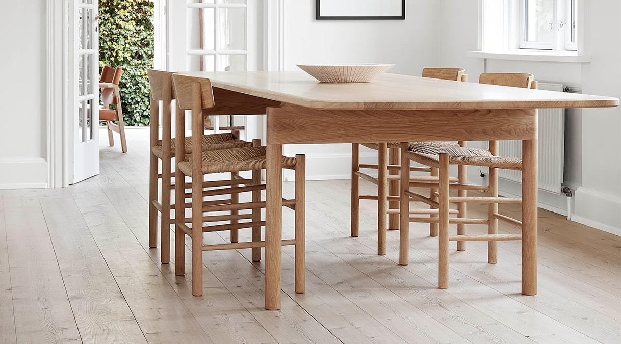 Post 6440 Dining Table - With its long rectangular table top and sturdy cylindrical legs, the Post Table is the perfect merging of functionality, simplicity and serenity in a classic design expressed with modern minimalism. The structural frame is exceptionally crafted in solid wood, teamed with a table top in solid oak. Enjoy loads of leg room in the wide space between the legs on either end, adding to the appeal of this practical, tactile table for dining or meeting in a residential, corporate or hospitality setting.  The Post Collection is an example of eliminating anything extra in order to solely focus on the essential. For designer Cecilie Manz, creating is about examining the purpose of a piece of furniture. Stripping the concept down to only what's necessary, the form emerges from the function in an expression that's pure and purposeful.  It's this simplicity imbued with a sense of beauty that is at the core of the new Post Collection from Manz. The name is a nod to the former home of the Royal Mail, renovated into our flagship showroom in Copenhagen Clean, uncluttered lines are the signature traits of the Post Table and Post Chair, each boasting a solid wood frame that reflects our heritage of wood craftsmanship and appreciation for authentic materials.  The Post Chair is upright and unassuming, with clean, classic lines. The plywood seat and back are light yet sturdy, while the arms offer just enough support with a minimal use of space. Add to that the option of an upholstered seat in leather or fabric, and you have a subtle design that could easily fit into a residential setting, restaurant, café or corporate environment.   The perfect partner is the Post Table, featuring a long rectangular table top and matching cylindrical legs. The solid wood frame provides a stable structure for the streamlined table top available in solid oak. Given the placement of the legs on either end, the result is loads of leg room. An extra advantage to the appeal of this prac